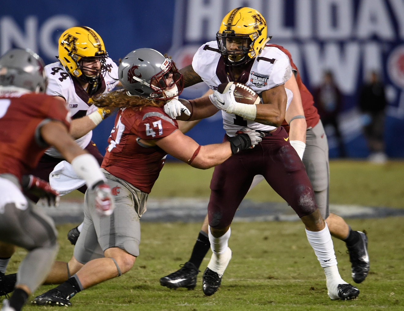 Minnesota running back Rodney Smith (1) breaks the tackle of Washington State linebacker Peyton Pelluer (47) during the first half of the Holiday Bowl NCAA college football game, Tuesday, Dec. 27, 2016, in San Diego. (AP Photo/Denis Poroy)