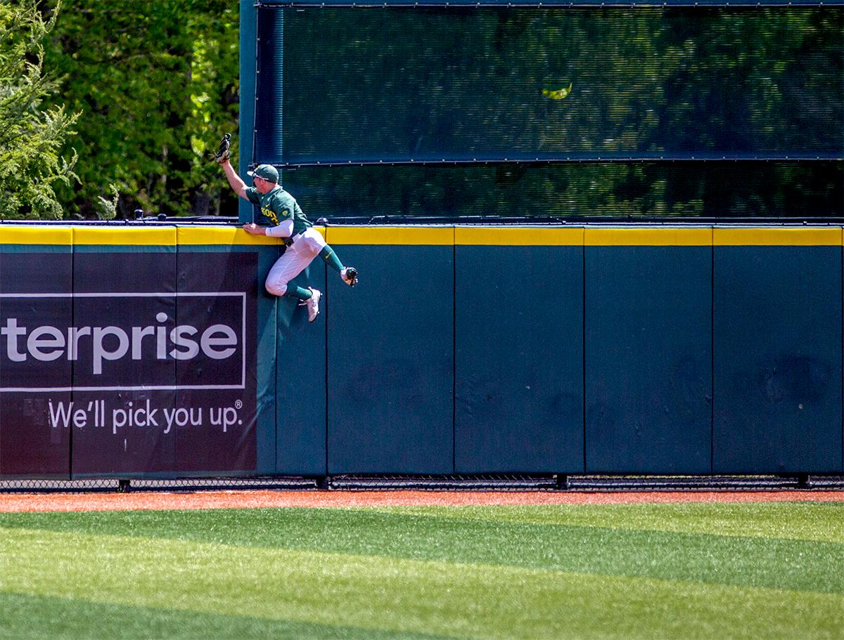 The Duck's Jake Bennett (#32) jumps above the fence in an attempt to catch a home run. The Duck?s defeated the Arizona State Sun Devils 3-2 on Sunday in the final game of the three-game series to close out the series with two wins and one loss. Jacob Bennett (#16) gave the Ducks their first point in the third inning. Kyle Kasser (#9) and Morgan McCullough (#1) added two more points in the 4th inning to give the Ducks enough of a lead to hold off the Sun Devils to the end of the ninth. Photo by August Frank, Oregon News Lab