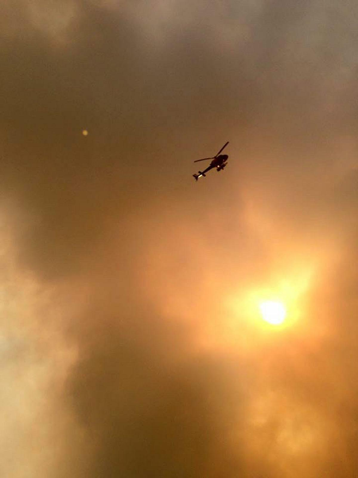 Smoke fills the air as a helicopter flies overhead in Fort McMurray, Alberta on Tuesday, May 3, 2016. The entire population of the Canadian oil sands city of Fort McMurray, has been ordered to evacuate as a wildfire whipped by winds engulfed homes and sent ash raining down on residents.  (Kitty Cochrane/The Canadian Press via AP) MANDATORY CREDIT