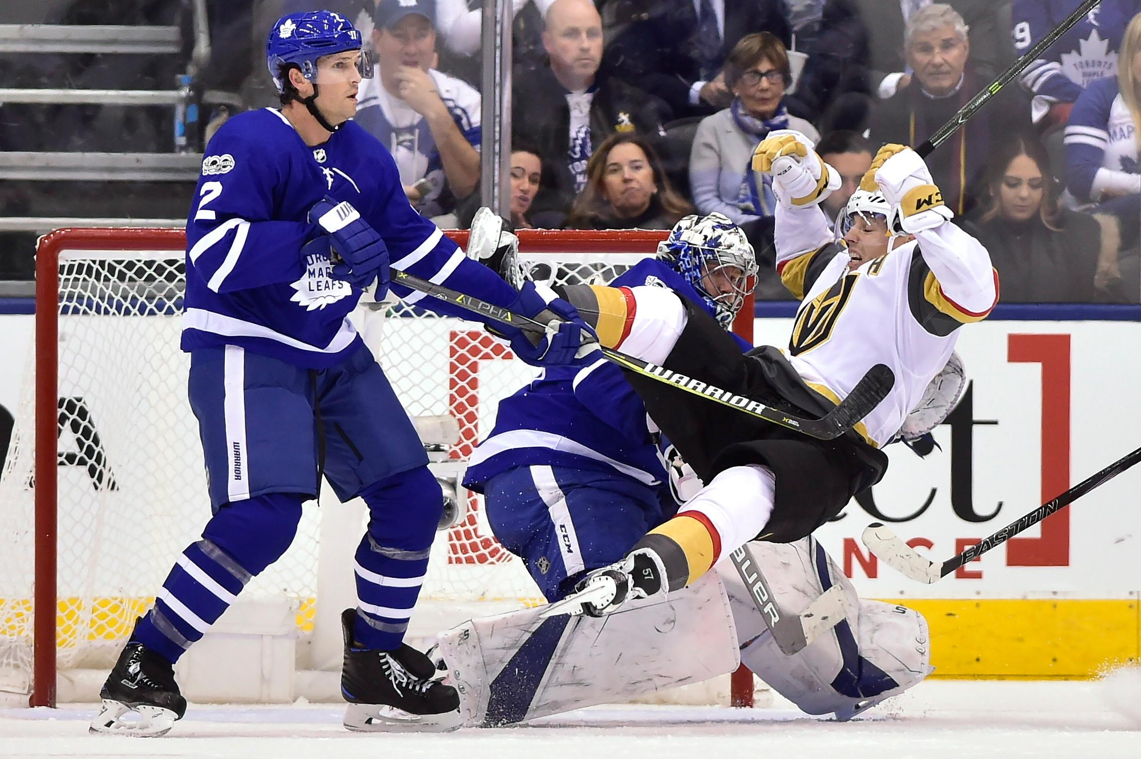 Vegas Golden Knights left wing David Perron (57) falls over Toronto Maple Leafs goalie Frederik Andersen (31) as defenseman Ron Hainsey (2) defends during the second period of an NHL hockey game, Monday, Nov. 6, 2017, in Toronto. (Frank Gunn/The Canadian Press via AP)