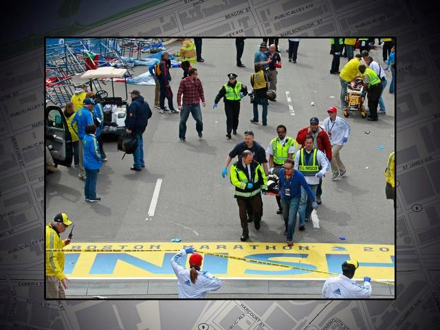 Medical workers carry injured across the finish line following explosions at the 2013 Boston Marathon.