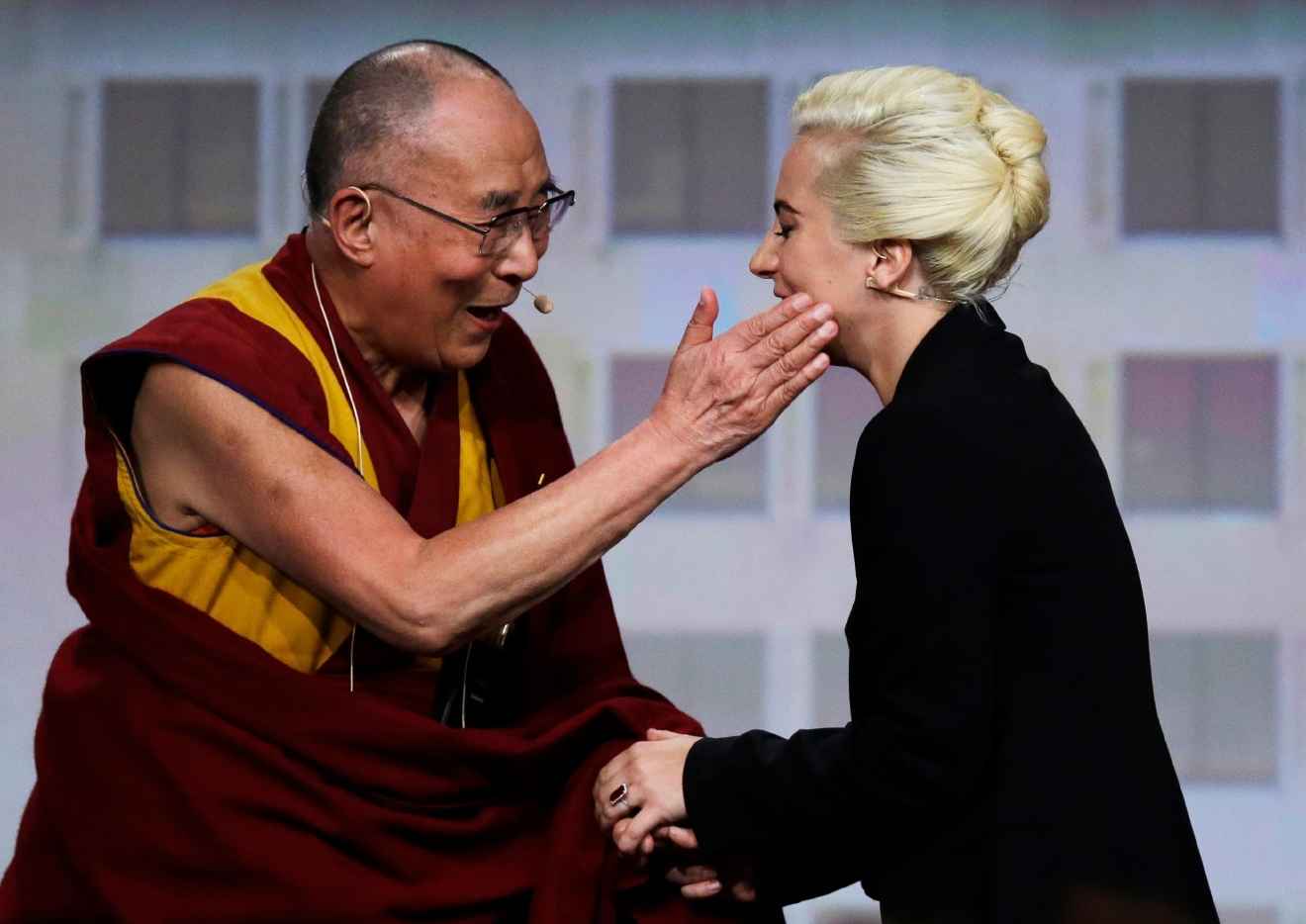 The Dalai Lama greets Lady Gaga, right, before a question and answer session at the U.S. Conference of Mayors in Indianapolis, Sunday, June 26, 2016. (AP Photo/Michael Conroy)