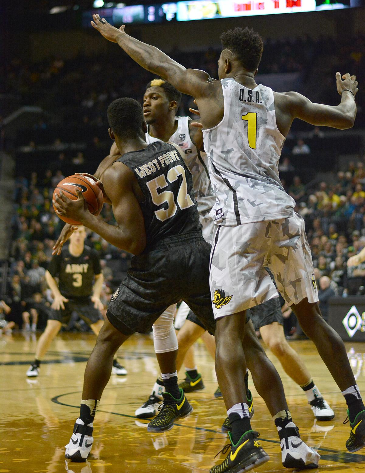 Army's John Emezie (#52) is heavily defended by Ducks' Jordan Bell (#1) and Dylan Ennis (#31). In front of a sold out crowd, Oregon defeated Army 91-77 on opening night. Photo by Jacob Smith, Oregon News Lab