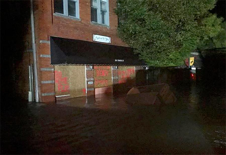 In this photo released by the New Bern Police department, flood waters move near buildings in downtown New Bern, N.C. on Friday, Sept. 14, 2018 as Hurricane Florence comes ashore. (New Bern Police Department via AP)