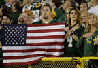 Fans hold a flag during the national anthem before a game between the Green Bay Packers and the Chicago Bears Thursday, Sept. 28, 2017, in Green Bay.