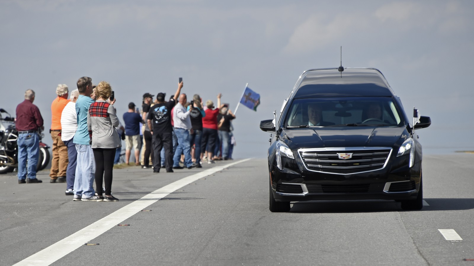 People watch as the hearse carrying the body of Billy Graham leaves Hickory, N.C., as it drives toward the Billy Graham Library Saturday, Feb. 24, 2018. Graham's body was brought to his hometown of Charlotte on Saturday, Feb. 24, as part of a procession expected to draw crowds of well-wishers. (Kathy Kmonicek/pool photo