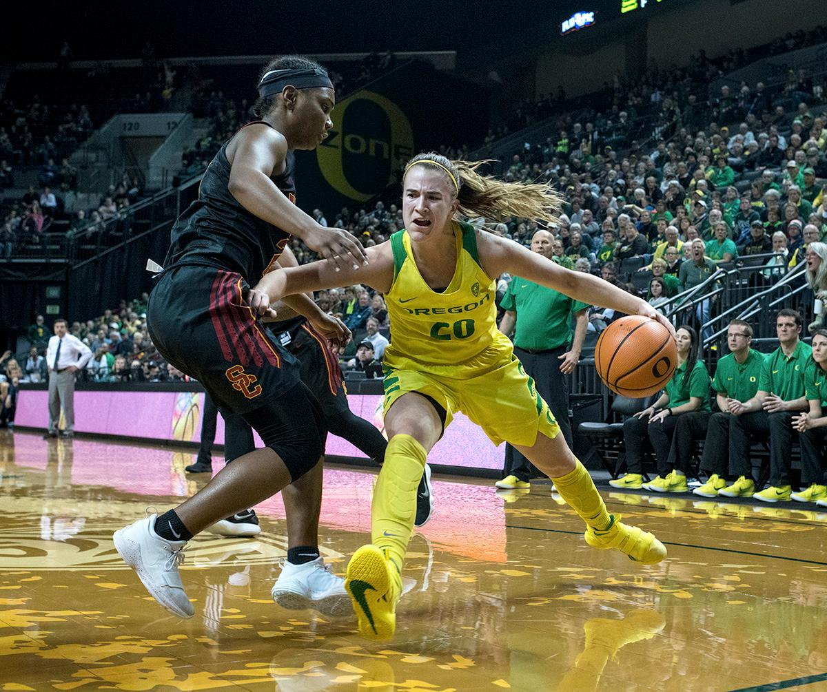 Oregon Ducks Sabrina Ionescu (#20) dribbles her way down the baseline. The Oregon Ducks defeated the USC Trojans 80-74 on Friday at Matthew Knight Arena in a game that went into double overtime. Lexi Bando sealed the Ducks' victory by scoring a three-pointer in the closing of the game. Ruthy Hebard set a new NCAA record of 30 consecutive field goals in three straight games, the old record being 28. Ruthy Hebard got a double-double with 27 points and 10 rebounds, Mallory McGwire also had 10 rebounds. The Ducks had four players in double digits. The Ducks are now 24-4, 13-2 in the Pac-12, and are tied for first with Stanford. Photo By Rhianna Gelhart, Oregon News Lab