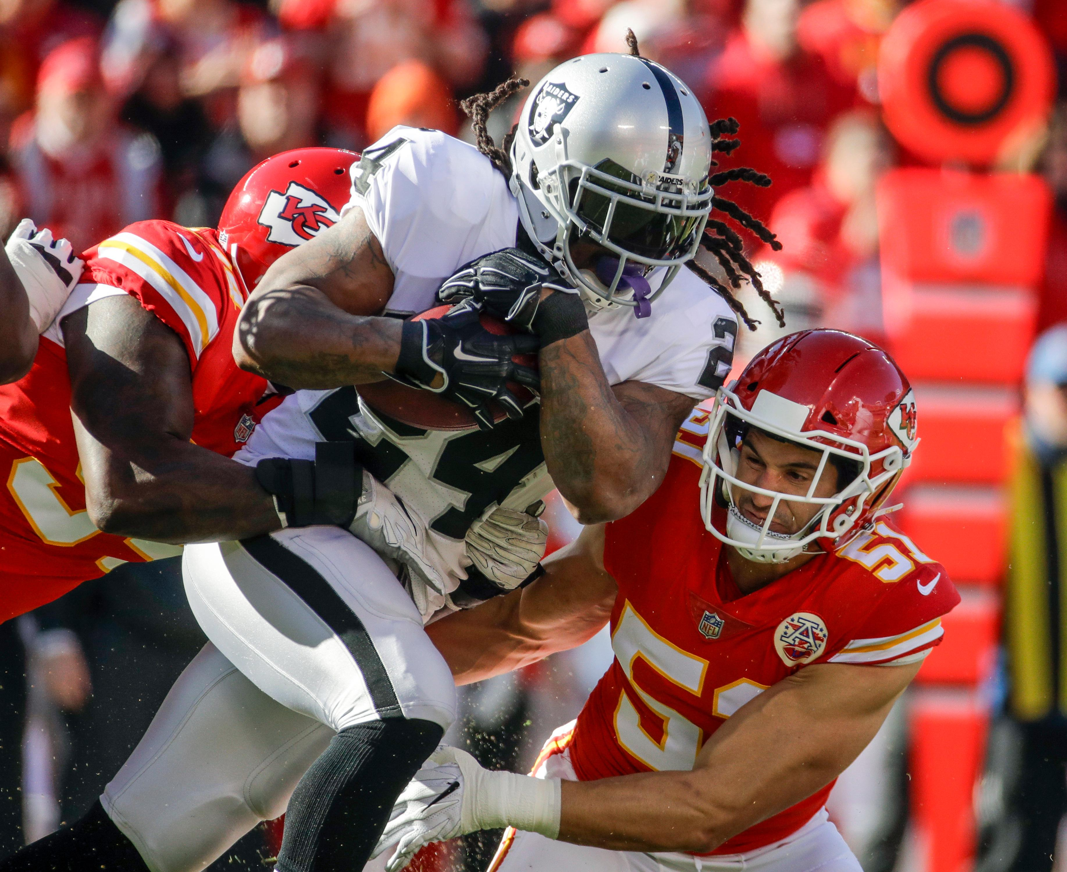 Oakland Raiders running back Marshawn Lynch (24) is tackled by Kansas City Chiefs linebacker Frank Zombo (51) and defensive lineman Jarvis Jenkins (94) during the first half of an NFL football game in Kansas City, Mo., Sunday, Dec. 10, 2017. (AP Photo/Charlie Riedel)