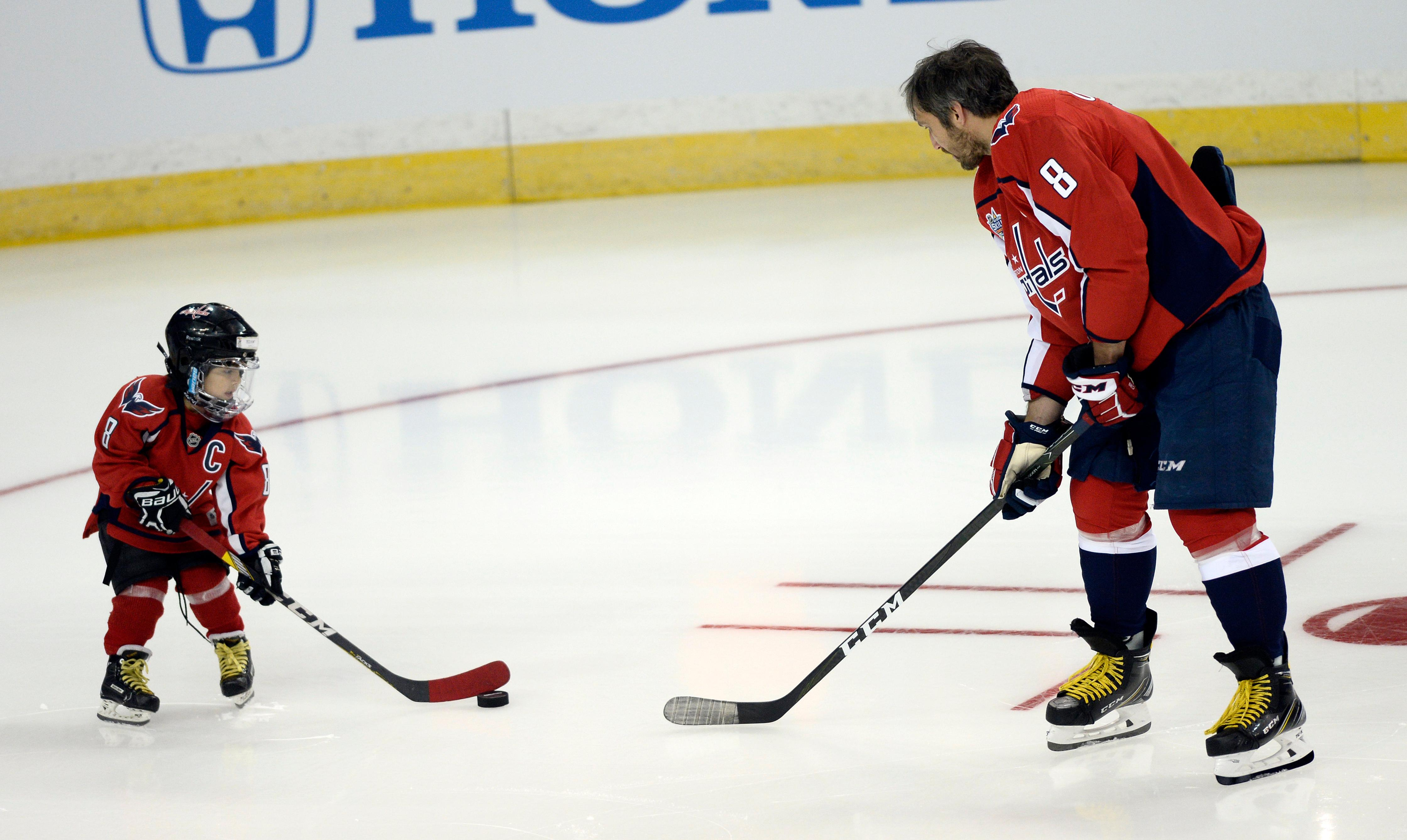 Washington Capitals forward Alexander Ovechkin (8) passes the puck to a young fan before the Skills Competition, part of the NHL All-Star Game events, Saturday, Jan. 27, 2018, in Tampa, Fla. (AP Photo/Jason Behnken)