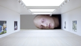People stick their heads into miniature galleries to become part of famous art exhibit