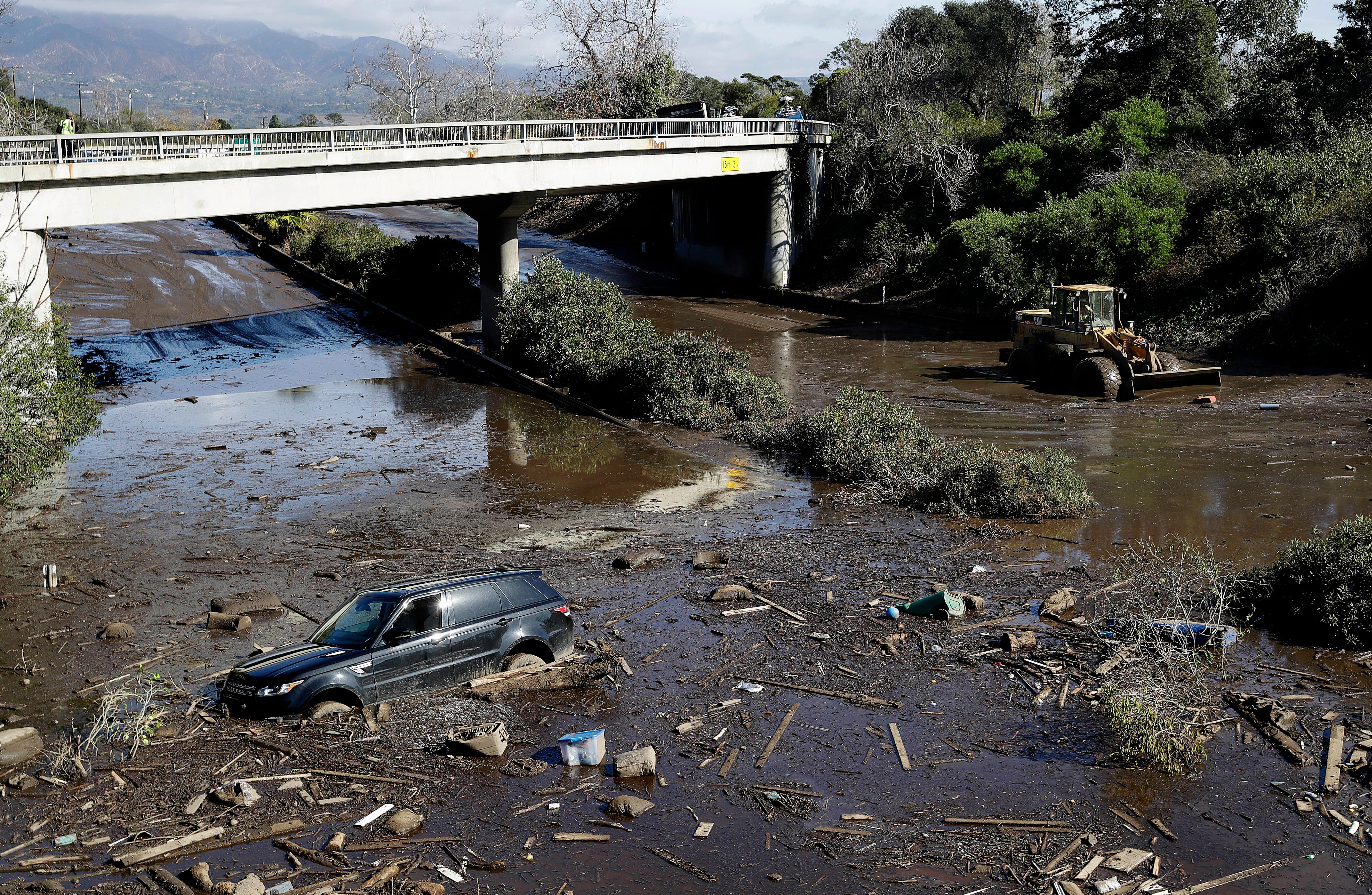 A bulldozer moves debris as a vehicle sits stranded in flooded water on U.S. Highway 101 in Montecito, Calif., Wednesday, Jan. 10, 2018. Dozens of homes were swept away or heavily damaged and several people were killed Tuesday as downpours sent mud and boulders roaring down hills stripped of vegetation by a gigantic wildfire that raged in Southern California last month. (AP Photo/Marcio Jose Sanchez)