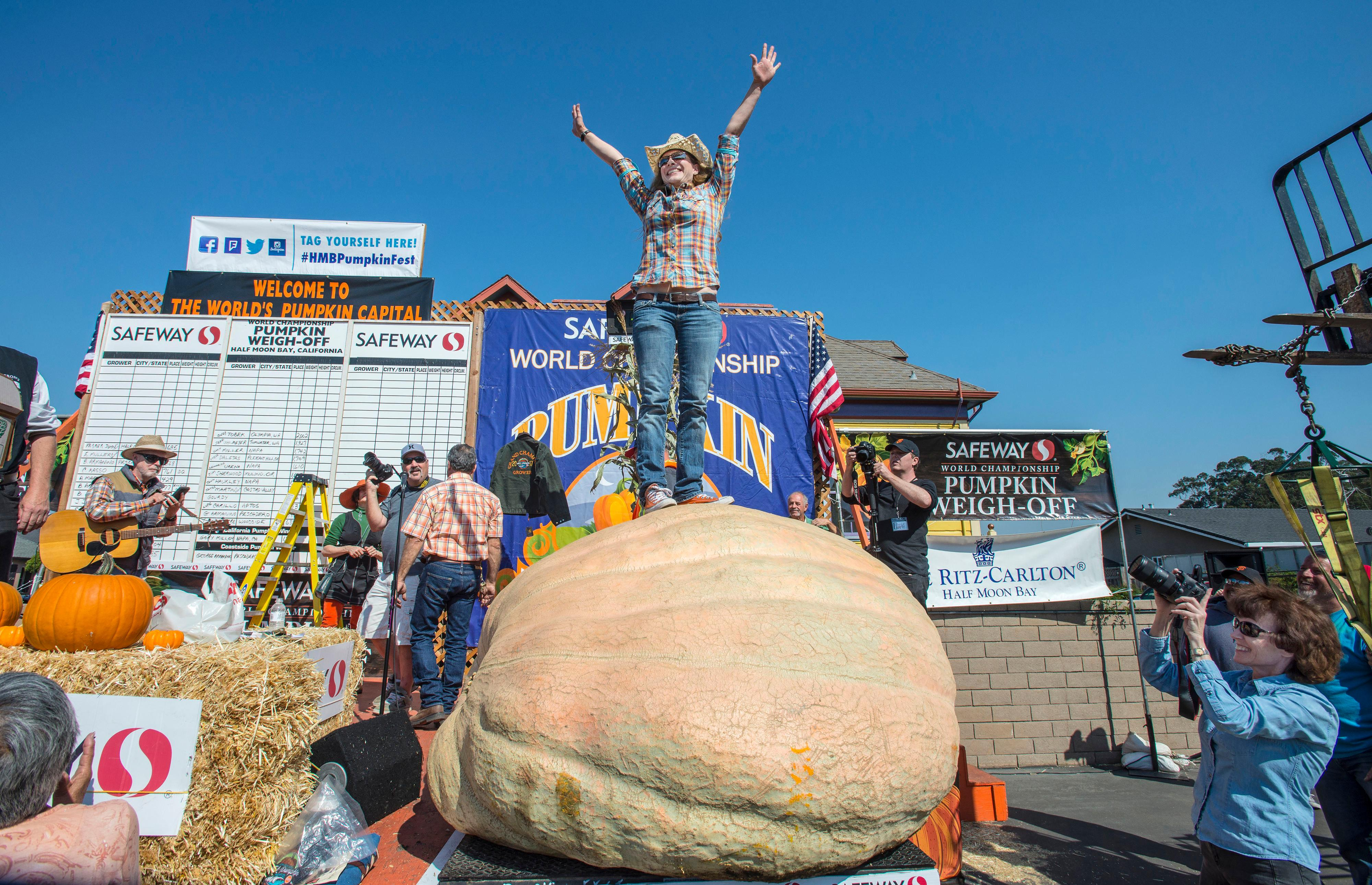 Cindy Tobek of Olympia, Wash., throws her arms into the air as she stands on her 2002 pound pumpkin at the 44th World Championship Pumpkin Weigh-Off in Half Moon Bay, Calif.,  on Monday, Oct.  9, 2017. Tobek finished in second place behind Joel Holland of Sumner, Wash. Holland's pumpkin weighed in at 2363 pounds.   (Mark Rightmire/The Orange County Register via AP)