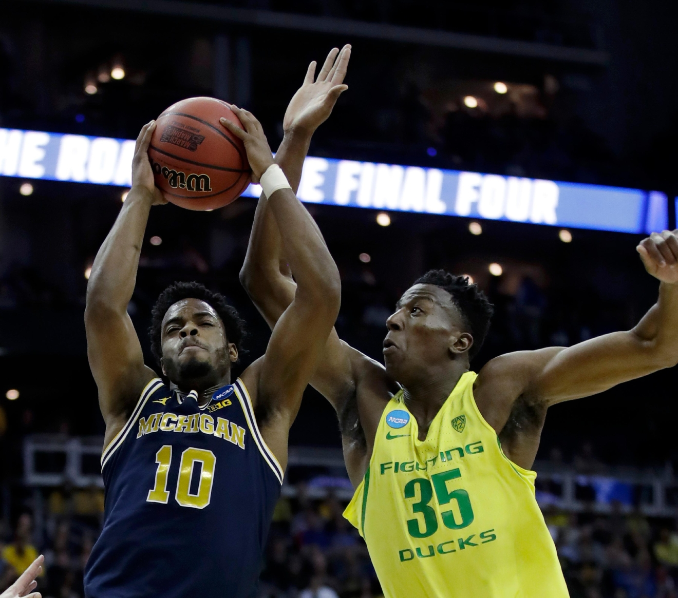 Michigan guard Derrick Walton Jr. (10) grabs a rebound next to Oregon forward Kavell Bigby-Williams during the first half of a regional semifinal of the NCAA men's college basketball tournament, Thursday, March 23, 2017, in Kansas City, Mo. (AP Photo/Charlie Riedel)