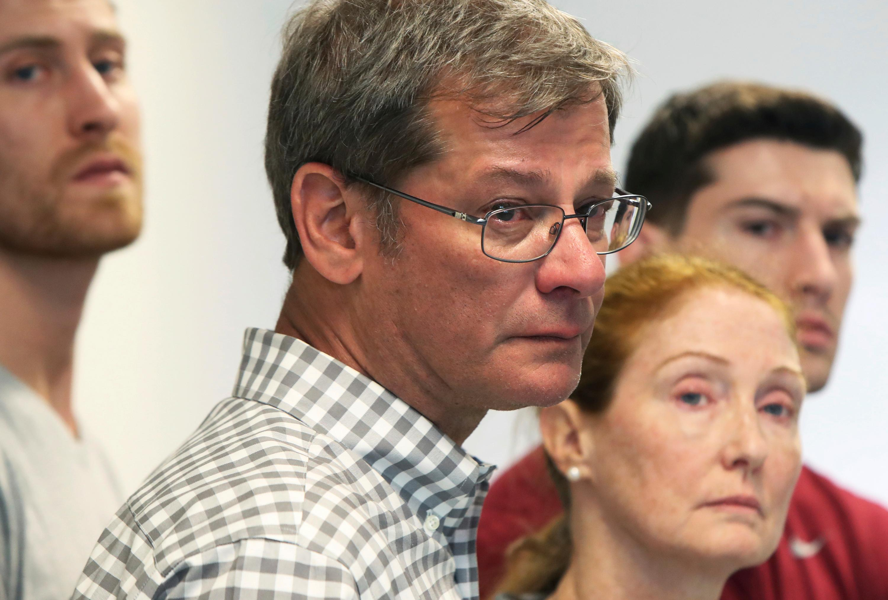 Parents John and Lisa Dombroski, center, stand with their sons John, left, and Kevin, right, during a press conference regarding their missing son and brother Mark, at the Hamilton Police Station in Hamilton, Bermuda, Monday, March 19, 2018. Mark Dombroski, 19, a member of the rugby team at Saint Joseph's University in Philadelphia, disappeared early Sunday after a night of socializing at the end of an international rugby tournament. (Blaire Simmons/The Royal Gazette via AP)