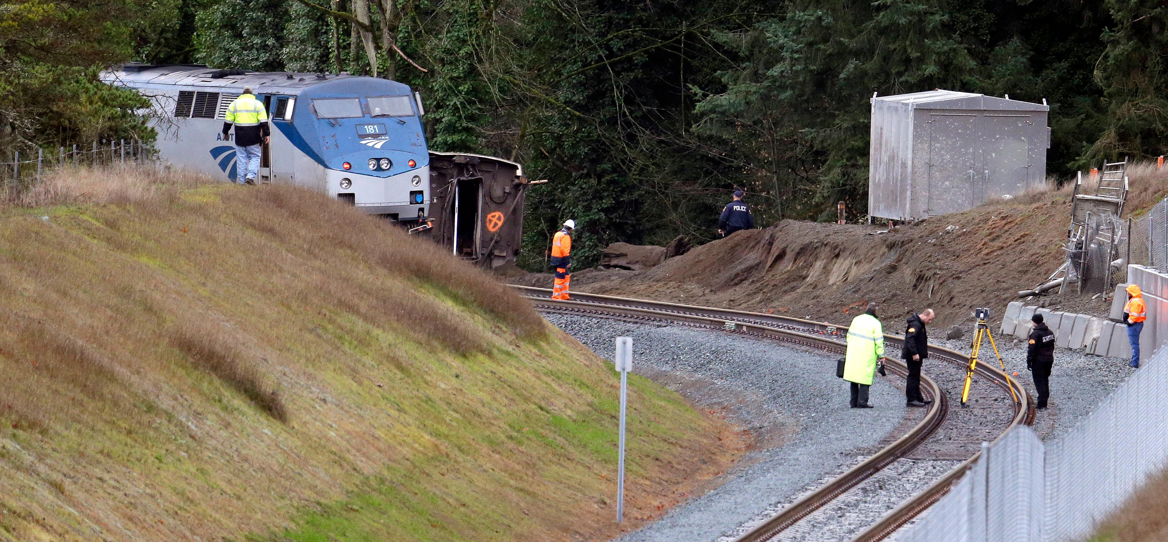 Cars from an Amtrak train remain on the tracks above where other cars spilled below onto Interstate 5 Monday, Dec. 18, 2017, in DuPont, Wash. The Amtrak train making the first-ever run along a faster new route hurtled off the overpass Monday near Tacoma and spilled some of its cars onto the highway below, killing some people, authorities said. Seventy-eight passengers and five crew members were aboard when the train moving at more than 80 mph derailed about 40 miles south of Seattle before 8 a.m., Amtrak said. (AP Photo/Elaine Thompson)