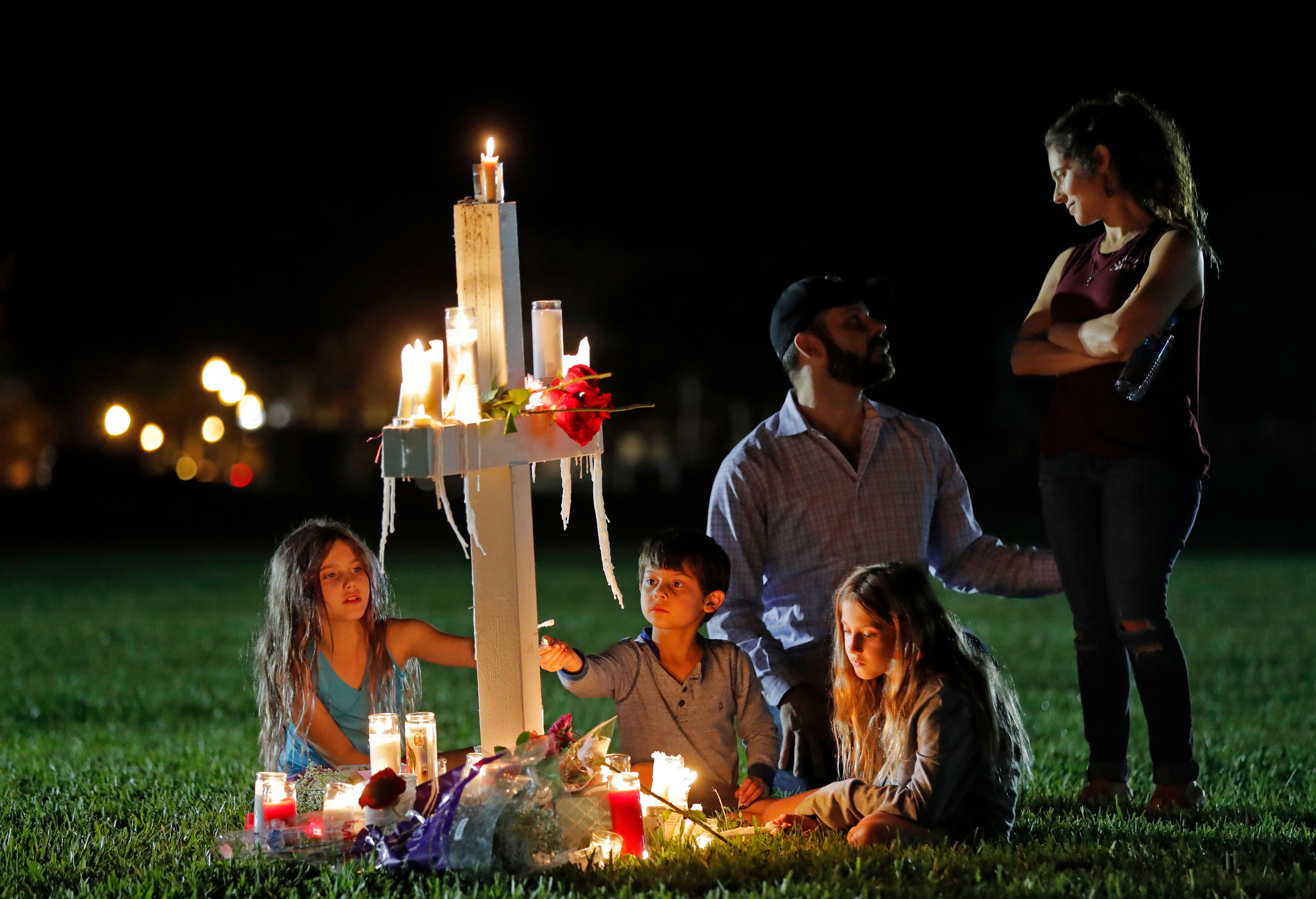 Rich and Rachel Castleberry visit one of seventeen crosses after a candlelight vigil for the victims of the Wednesday shooting at Marjory Stoneman Douglas High School, in Parkland, Fla., Thursday, Feb. 15, 2018. (AP Photo/Gerald Herbert)<p></p>