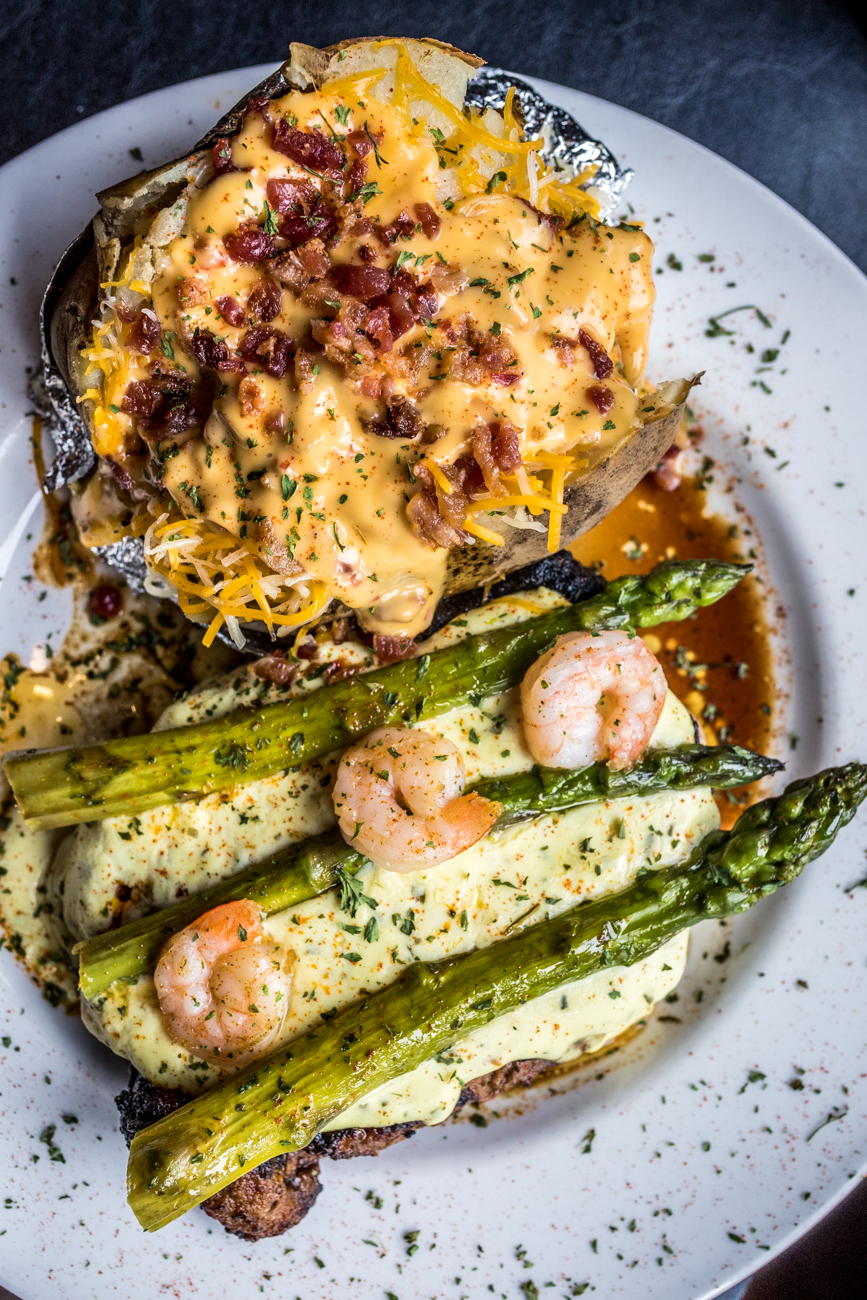 Oscar Rib-Eye: hand-cut and topped with shrimp, asparagus, and Bearnaise sauce served with a loaded baked potato / Image: Catherine Viox // Published: 8.10.20