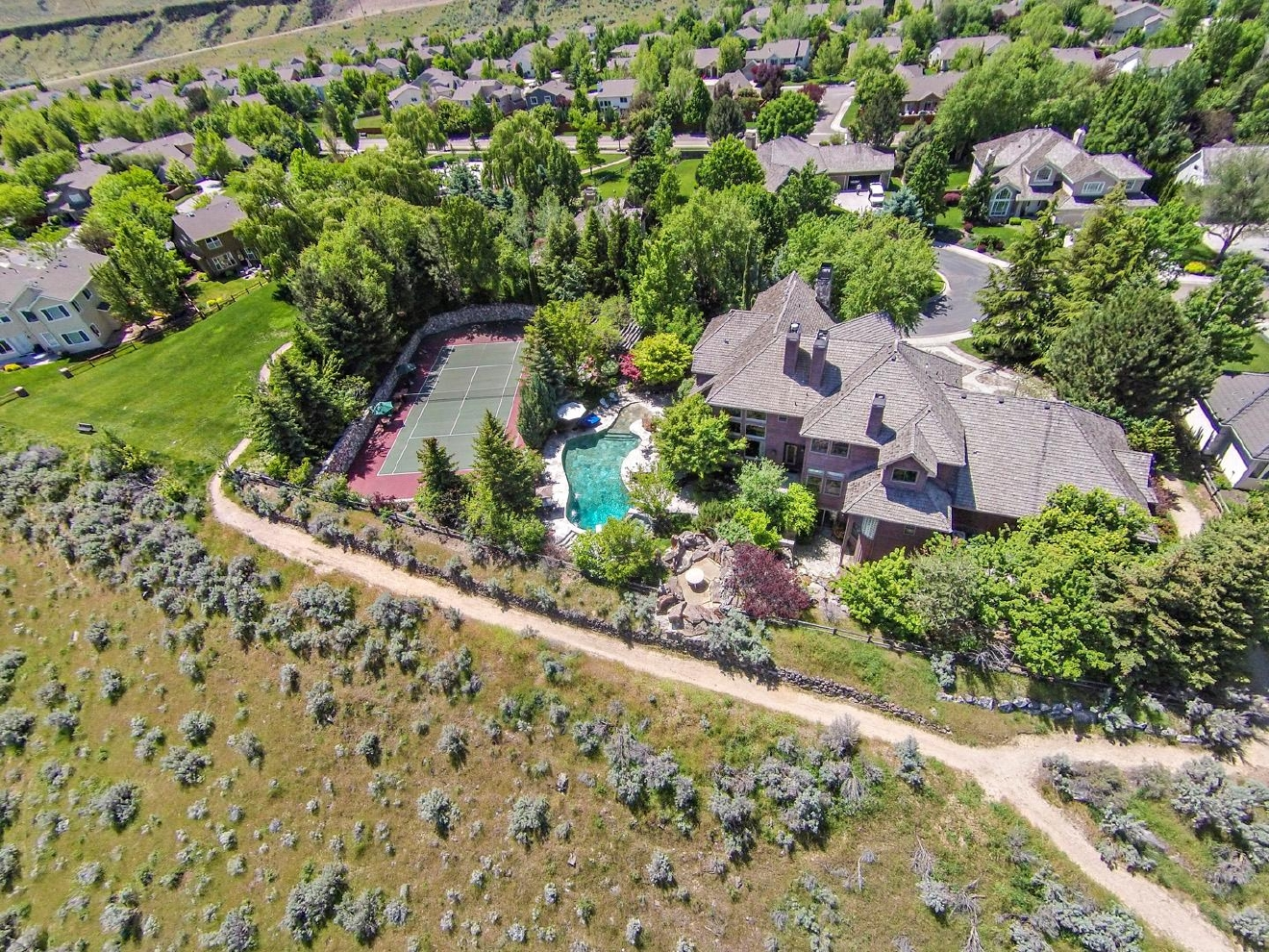 One of a kind! Rim View Estate Home on 3/4 acres with a resort-like backyard. Incredible panoramic views of the mountains, Barber Wildlife Preserve and downtown. Over 50 gorgeous mature trees surround the home. Original Flagstone Rock Pool & Spa, Sunken Tennis Court with imported rock walls, timbered cabana & stunning waterfall. The home boasts beautiful vaulted ceilings, two laundry rooms, workout room, wine closet, & more! Only 1/2 mile to the Greenbelt and the Boise River! | Information: John Yochum 208.336.3393 or email jyochum@coldwellbankertg.com