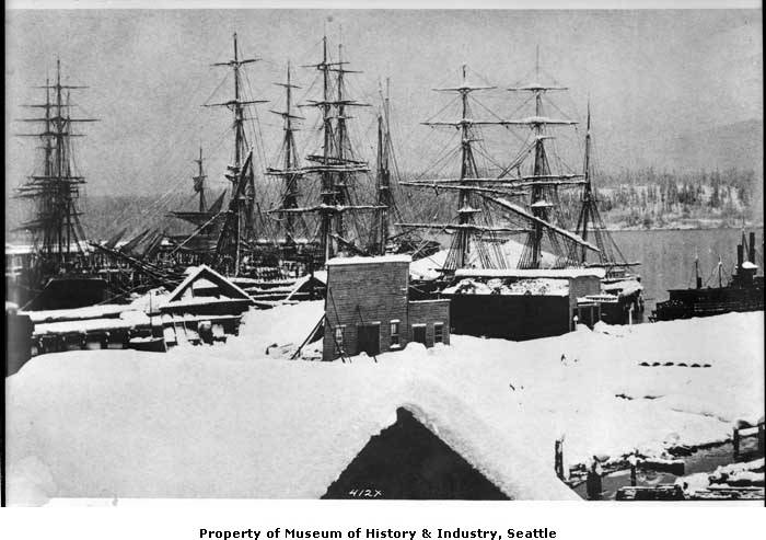 Seattle's record snowstorm began on January 5, 1880. Eight days later, the snow was a record 5 feet 4 inches deep. In this photo, the snow covers the rooftops, ship spars, and hillsides. The owner of the wooden building in the center tried to prop up his building with poles, but the snow was so heavy that the roof collapsed.  (Photo 1983.10.6117.1 // PEMCO Webster & Stevens Collection, Museum of History & Industry, Seattle)