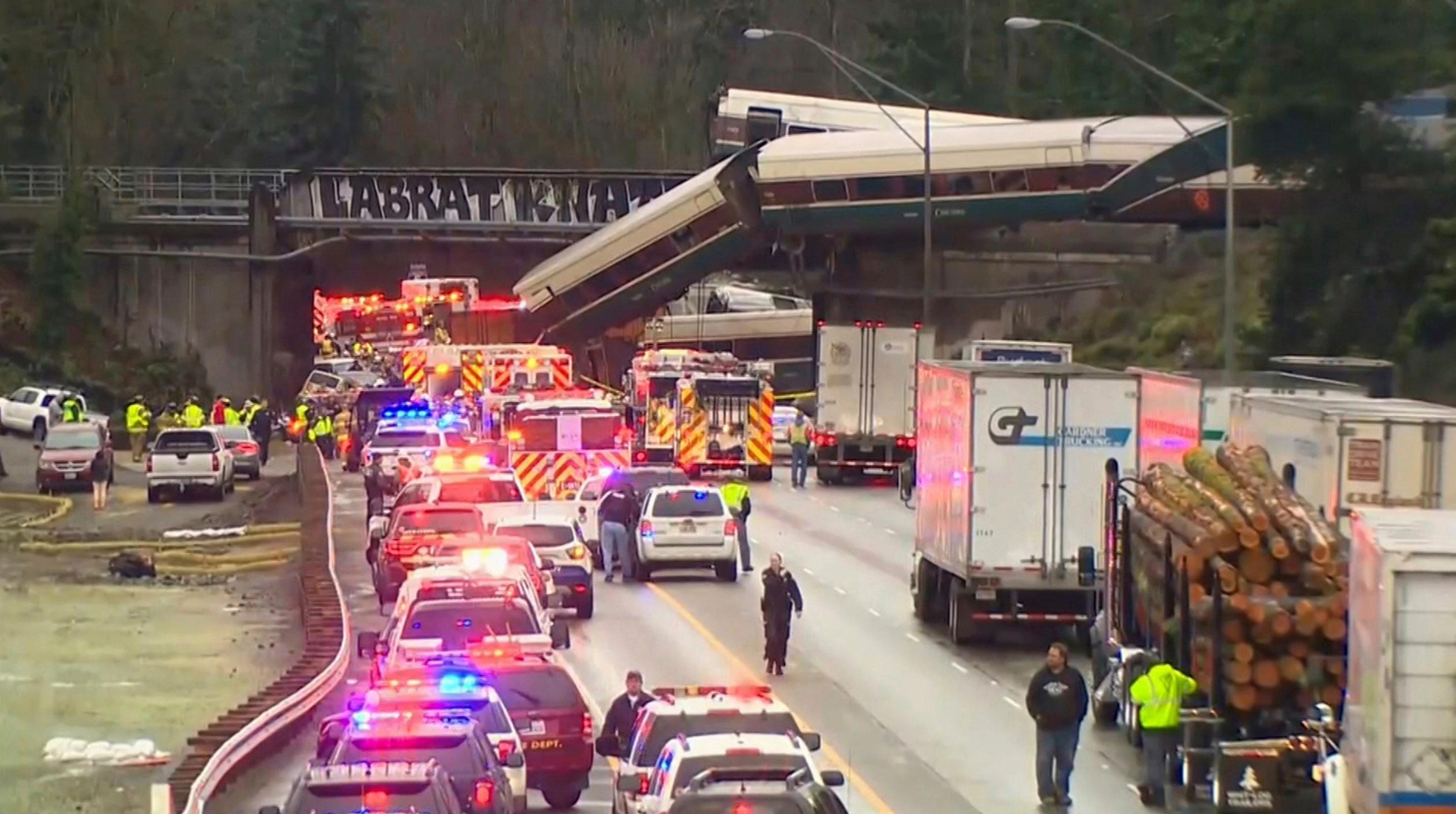 "In this still frame from video provided by KOMO-TV, first responders at the site of an Amtrak train that derailed south of Seattle on Monday, Dec. 18, 2017. Authorities reported ""injuries and casualties."" The train derailed about 40 miles (64 kilometers) south of Seattle before 8 a.m., spilling at least one train car on to busy Interstate 5. (KOMO-TV via AP) TV OUT MANDATORY CREDIT"