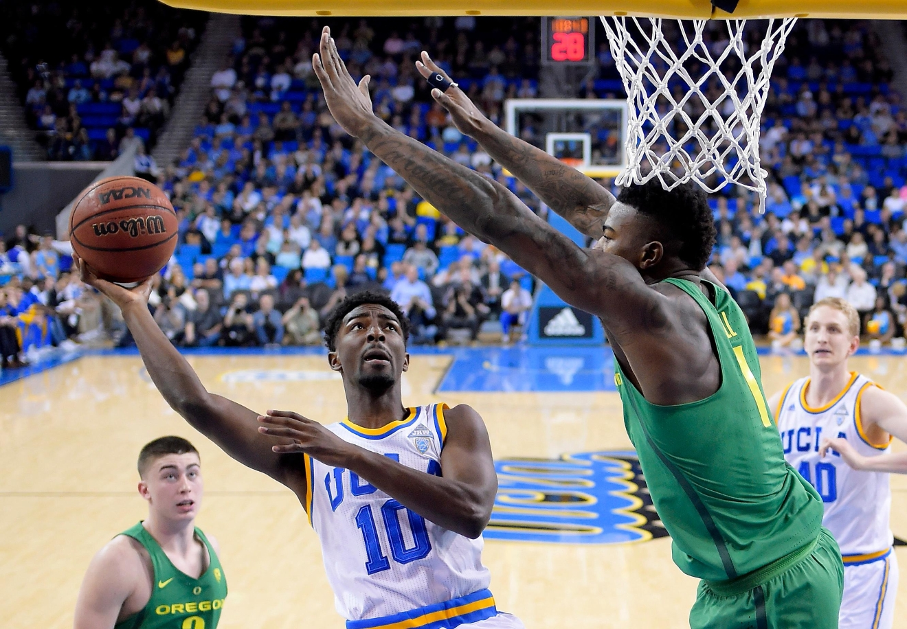 UCLA guard Isaac Hamilton, second from left, shoots as Oregon forward Jordan Bell defends during the first half of an NCAA college basketball game, Thursday, Feb. 9, 2017, in Los Angeles. (AP Photo/Mark J. Terrill)