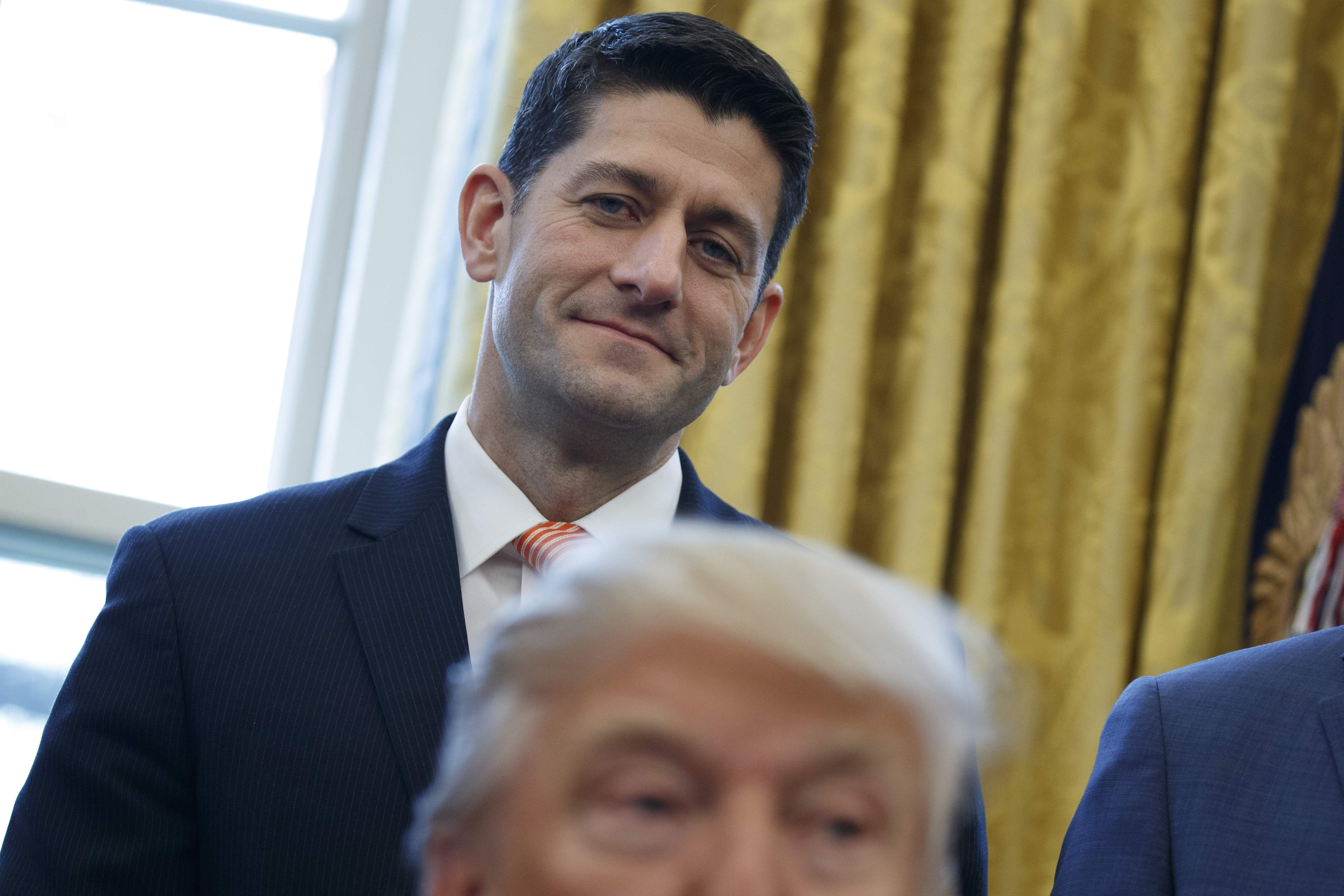 DAY 26 - In this Feb. 14, 2017, file photo, House Speaker Paul Ryan of Wis. watches as President Donald Trump signs House Joint Resolution 41, in the Oval Office of the White House in Washington. (AP Photo/Evan Vucci, File)