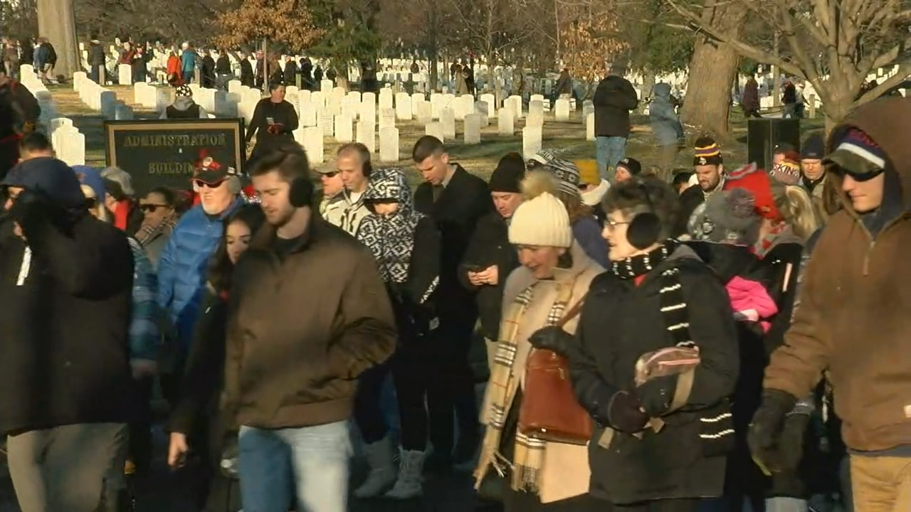 Over 50,000 volunteers lay wreaths on headstones at National Arlington Cemetery . (ABC7)