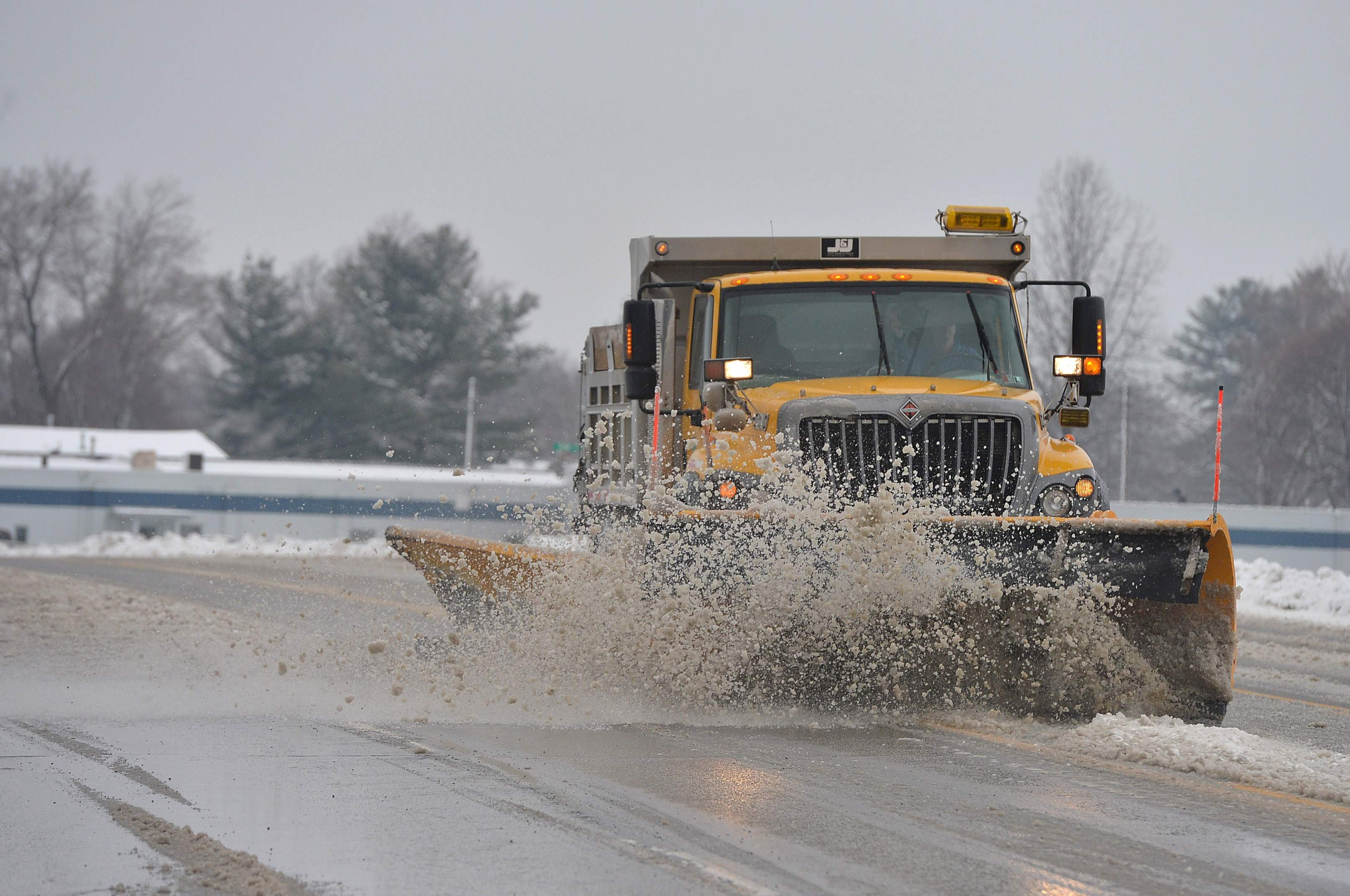 A PennDOT plow truck clears snow and slush from West 12th Street just east of the Erie International Airport in Millcreek Township, Erie County, Pa., on March 7, 2018 after a morning snow fall in the region. (AP Photo/Erie Times-News, Christopher Millette)