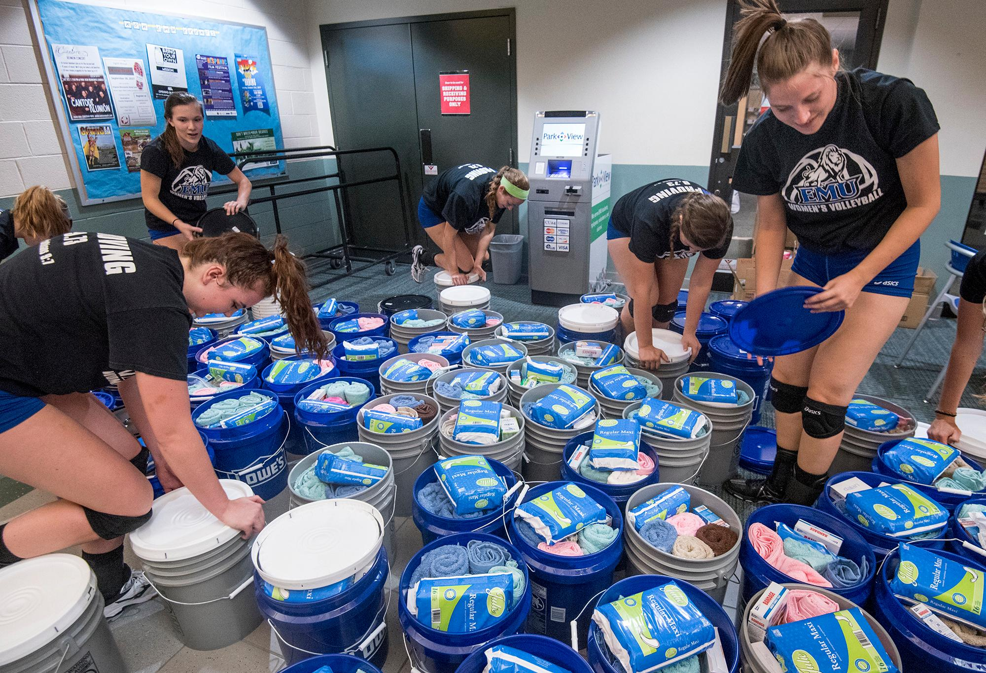 In this Sept. 25, 2017, photo, members of the community join the Eastern Mennonite University volleyball team as they pack buckets with relief kits bound for hurricane-ravaged Puerto Rico in Harrisonburg, Va. (Daniel Lin/Daily News-Record via AP)