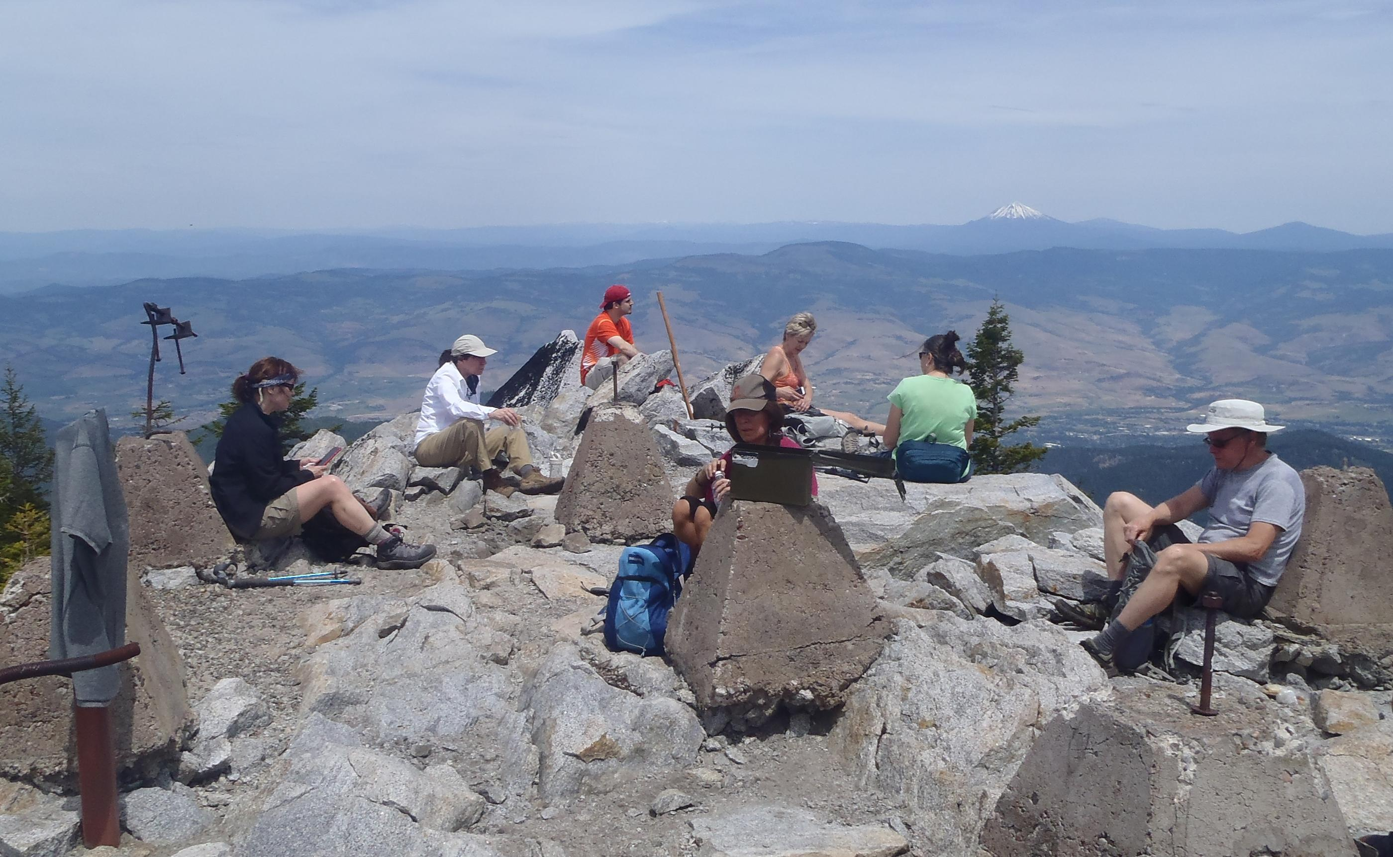 Hikers sprawl out atop Wagner Butte, the site of a former Forest Service lookout. Photo by Lee Juillerat