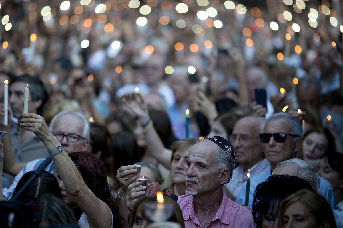 People hold candles during the one-year anniversary of prosecutor Alberto Nisman's death in Buenos Aires, Argentina, Monday, Jan. 18, 2016. Jewish rights groups have organized acts in several Argentine cities. Nisman was found dead in the bathroom of his Buenos Aires apartment on Jan. 18, 2015 with a bullet to his head hours before he was to detail to Congress his accusations that former President Cristina Fernandez and top administration officials orchestrated a secret deal with Iran to shield officials allegedly responsible for the the 1994 bombing of a Jewish community center that killed 85 people. (AP Photo/Natacha Pisarenko)