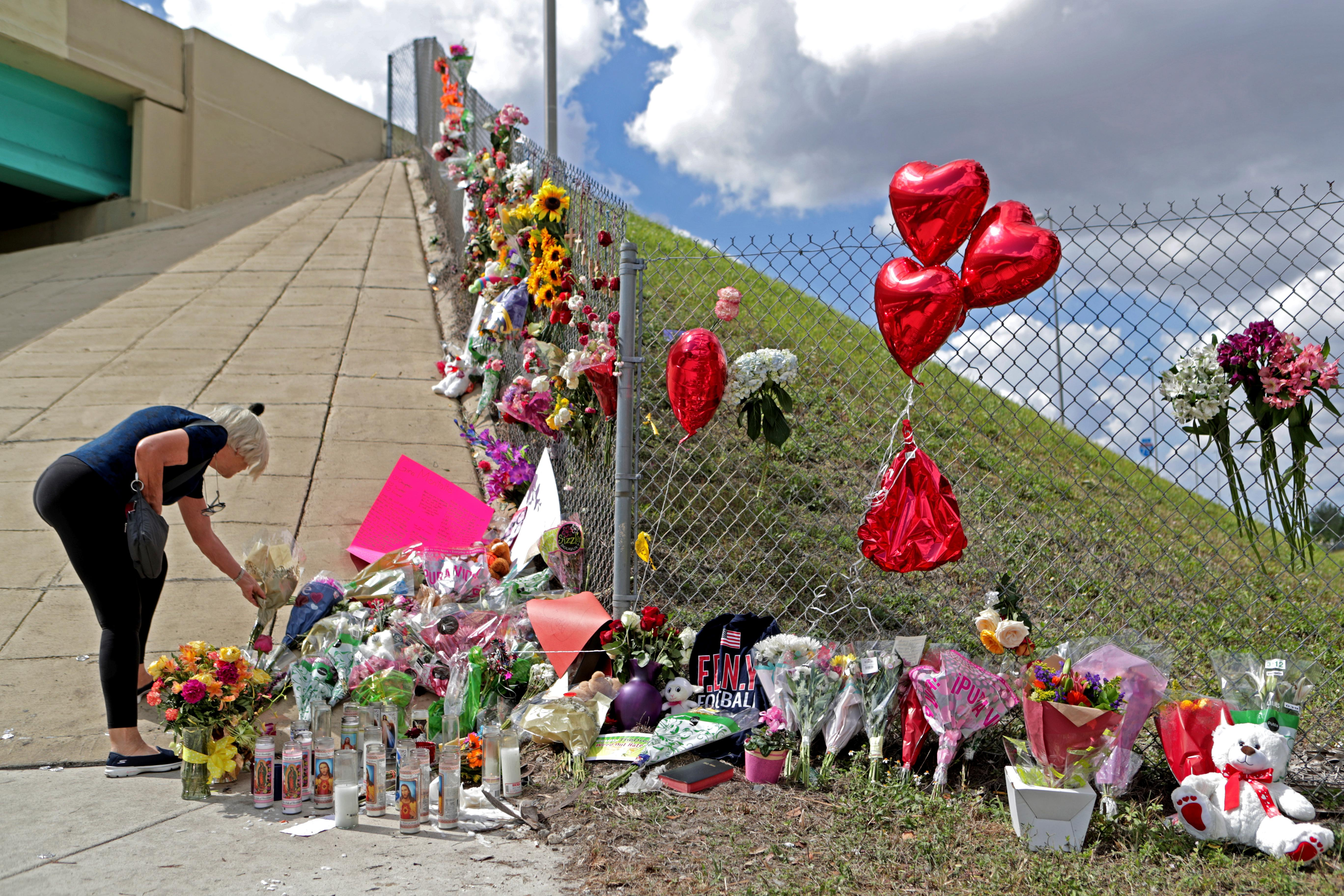 Ann Newman, of Deerfield Beach, Fla., a retired Broward County teacher, places flowers at a makeshift memorial at Marjory Stoneman Douglas High School in Parkland, Fla., Sunday, Feb. 18, 2018. Nikolas Cruz, a former student, was charged with 17 counts of premeditated murder on Thursday. (John McCall/South Florida Sun-Sentinel via AP)