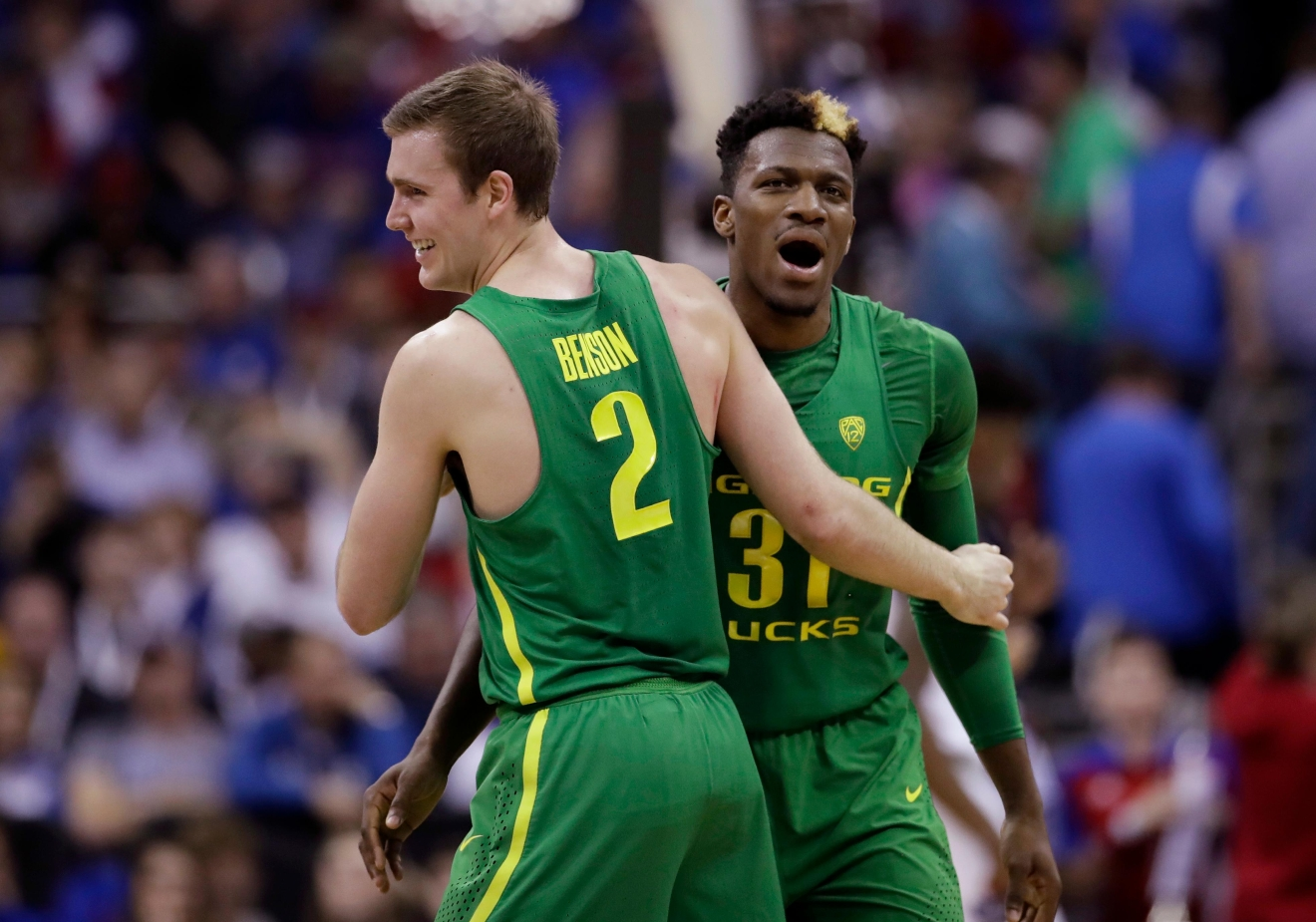 Oregon guard Casey Benson (2) celebrates with teammate Dylan Ennis at the end of the first half of the Midwest Regional final against Kansas in the NCAA men's college basketball tournament, Saturday, March 25, 2017, in Kansas City, Mo. (AP Photo/Charlie Riedel)