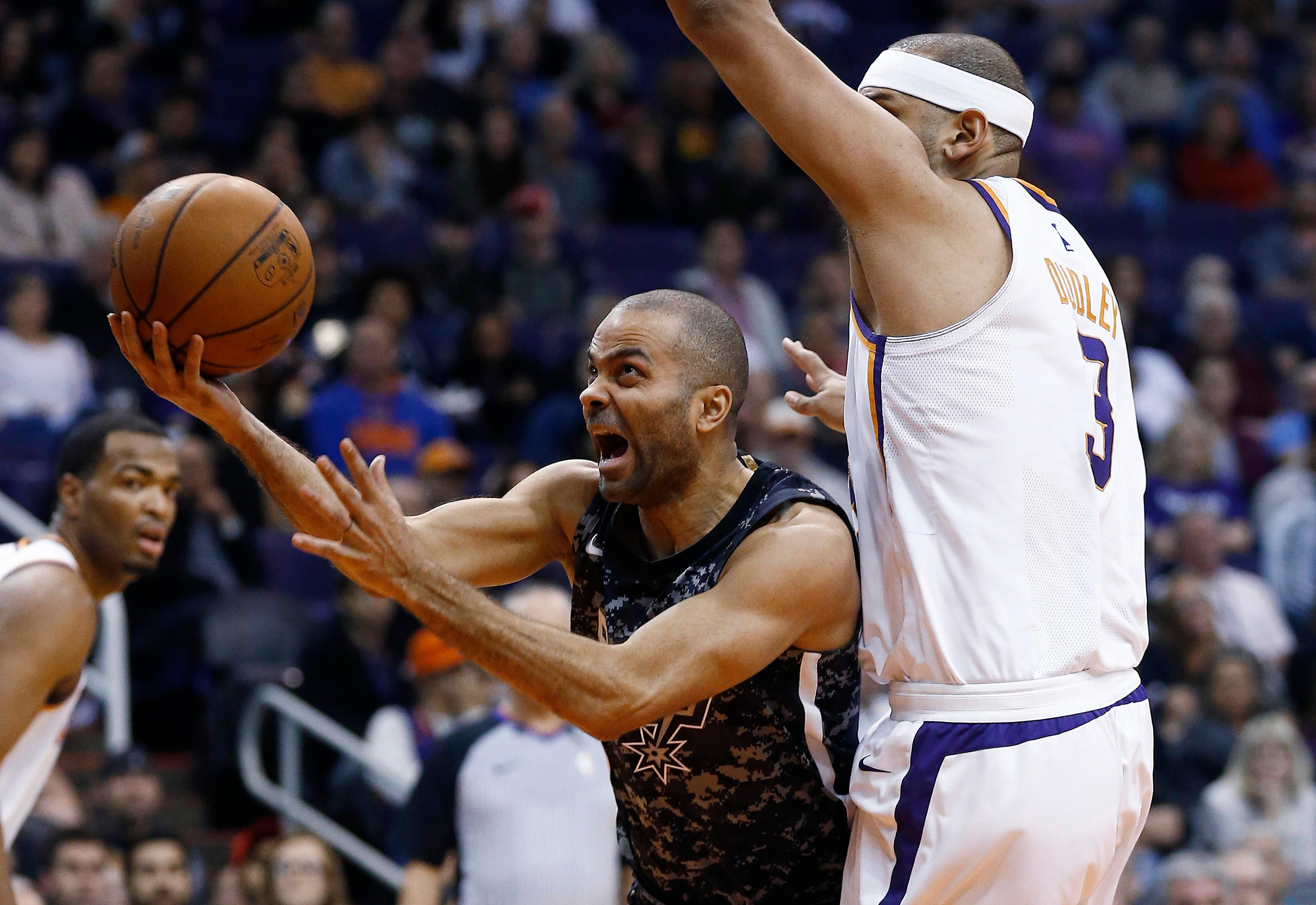 San Antonio Spurs guard Tony Parker, middle, is fouled as he drives past Phoenix Suns forward Jared Dudley (3) as Suns forward TJ Warren, left, watches during the first half of an NBA basketball game Wednesday, Feb. 7, 2018, in Phoenix. (AP Photo/Ross D. Franklin)