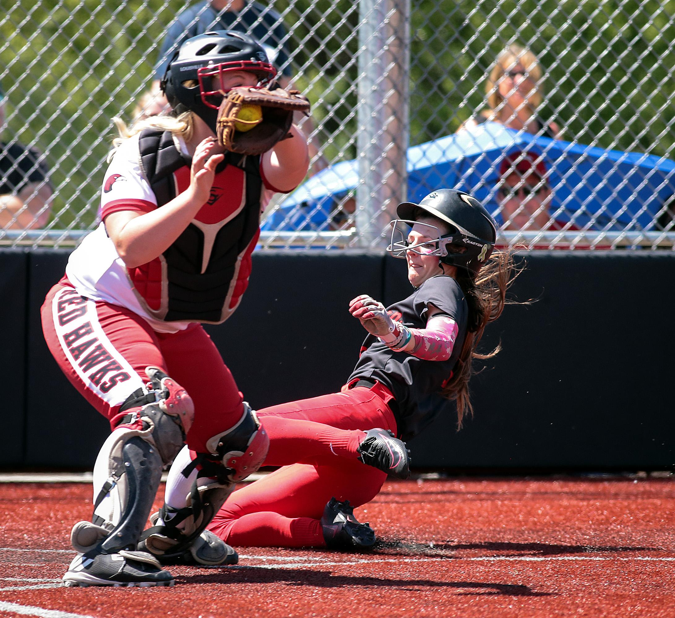 Southern Oregon University Kelsey Randall slides into home, for an In-the-Park Homerun, behind Simpson University catcher Kayla Bailey at US Cellular Fields on Monday.[PHOTO BY:  LARRY STAUTH JR]