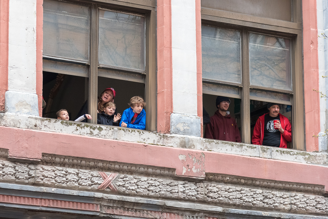 Reds fans joyfully look out onto the Opening Day Parade on Race Street. / Image: Phil Armstrong