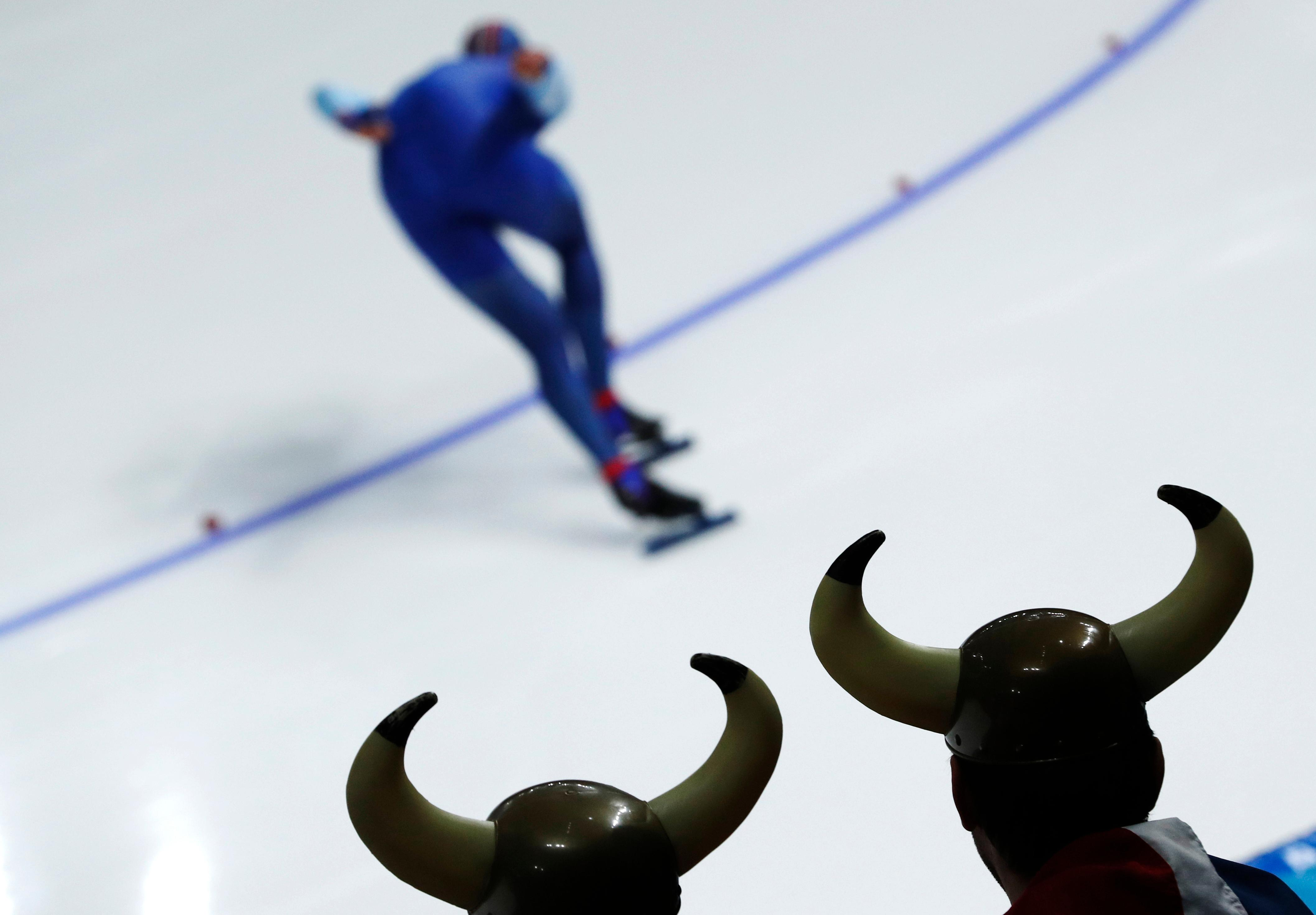 Two spectator dressed as Vikings watch as Havard Lorentzen of Norway competes during the men's 1,000 meters speedskating race at the Gangneung Oval at the 2018 Winter Olympics in Gangneung, South Korea, Friday, Feb. 23, 2018. (AP Photo/John Locher)