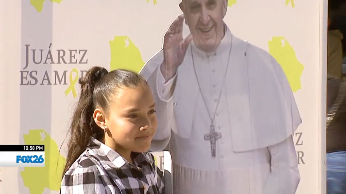 Taking pictures with a cardboard cutout of Pope Francis