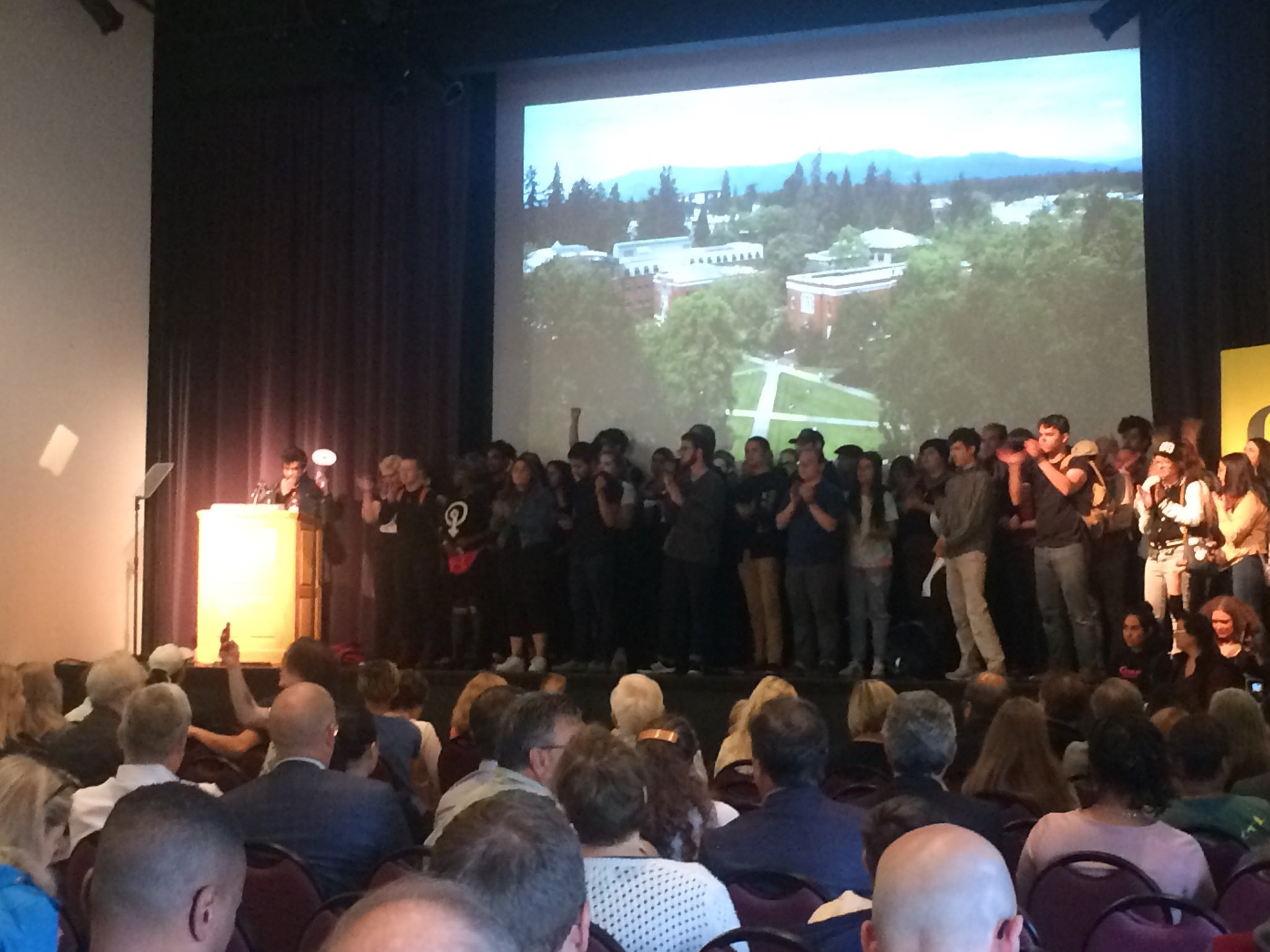 Students stormed the stage with a megaphone and sign ahead of University of Oregon President Michael Schill's State of the University address on Friday. (SBG)
