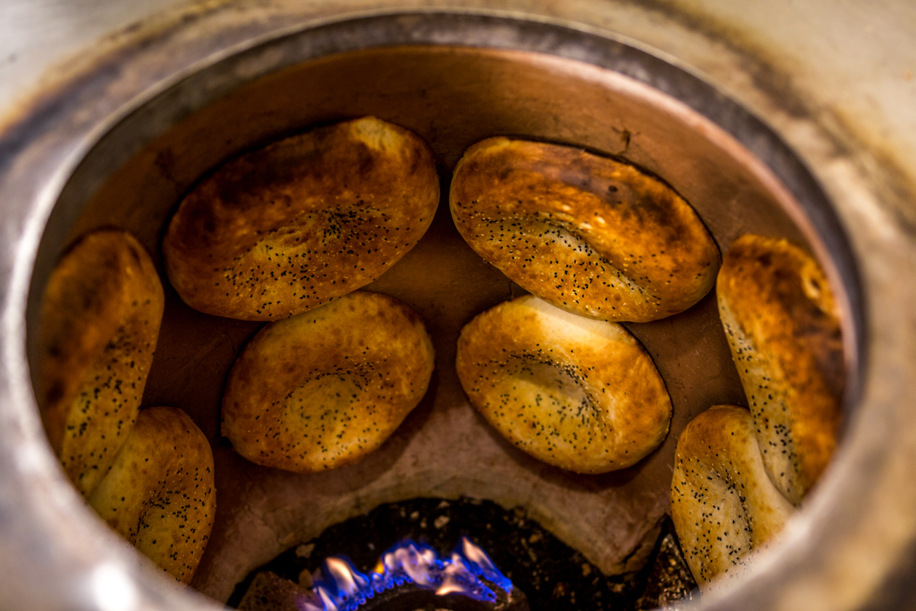 The house-made Uzbek bread is topped with sesame, beet butter, olive oil, and french sea salt and is baked in a tandoori style oven. / Image: Catherine Viox // Published: 9.5.19