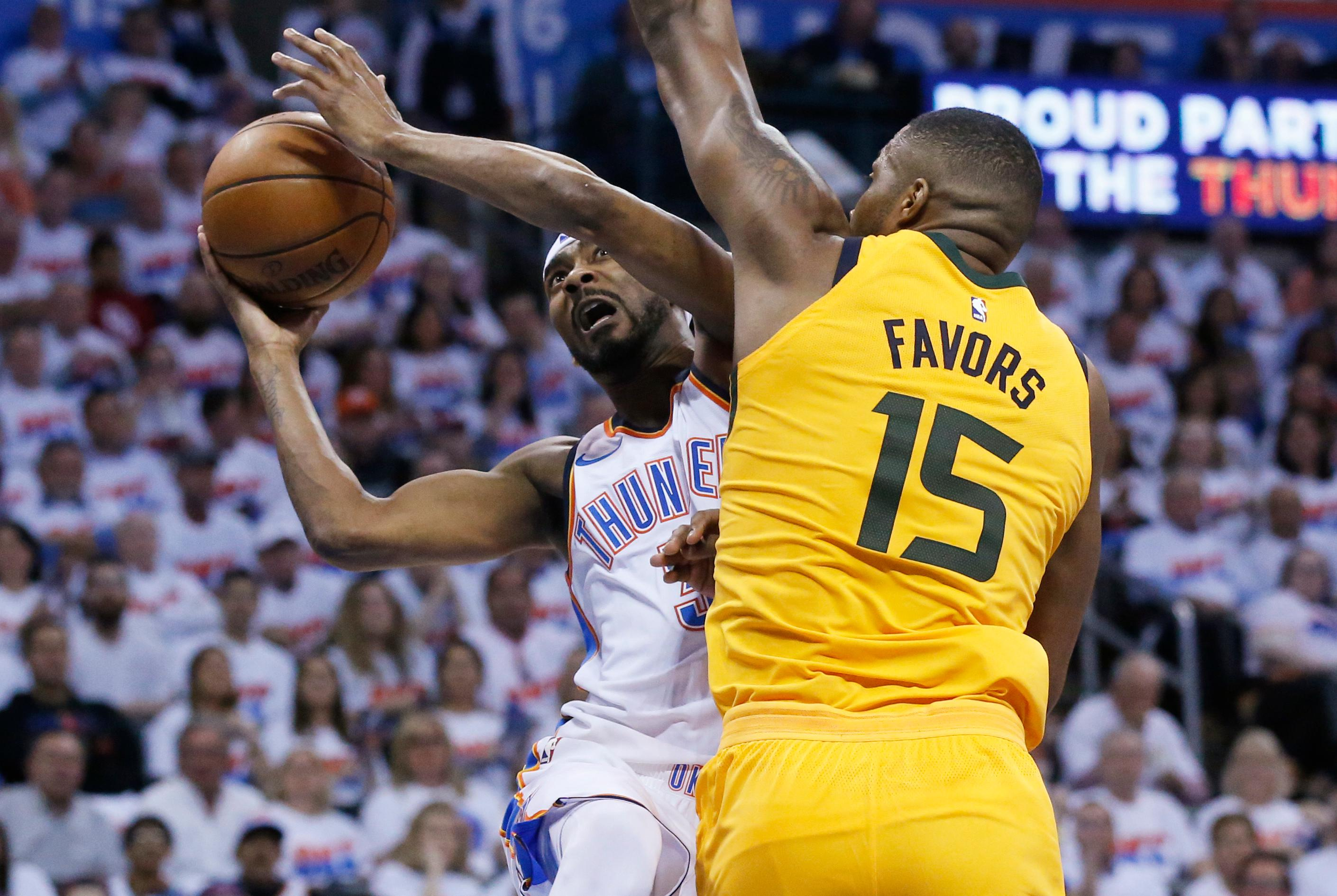 Oklahoma City Thunder forward Corey Brewer, left, shoots as Utah Jazz forward Derrick Favors (15) defends during the first half of Game 2 of an NBA basketball first-round playoff series in Oklahoma City, Wednesday, April 18, 2018. (AP Photo/Sue Ogrocki)