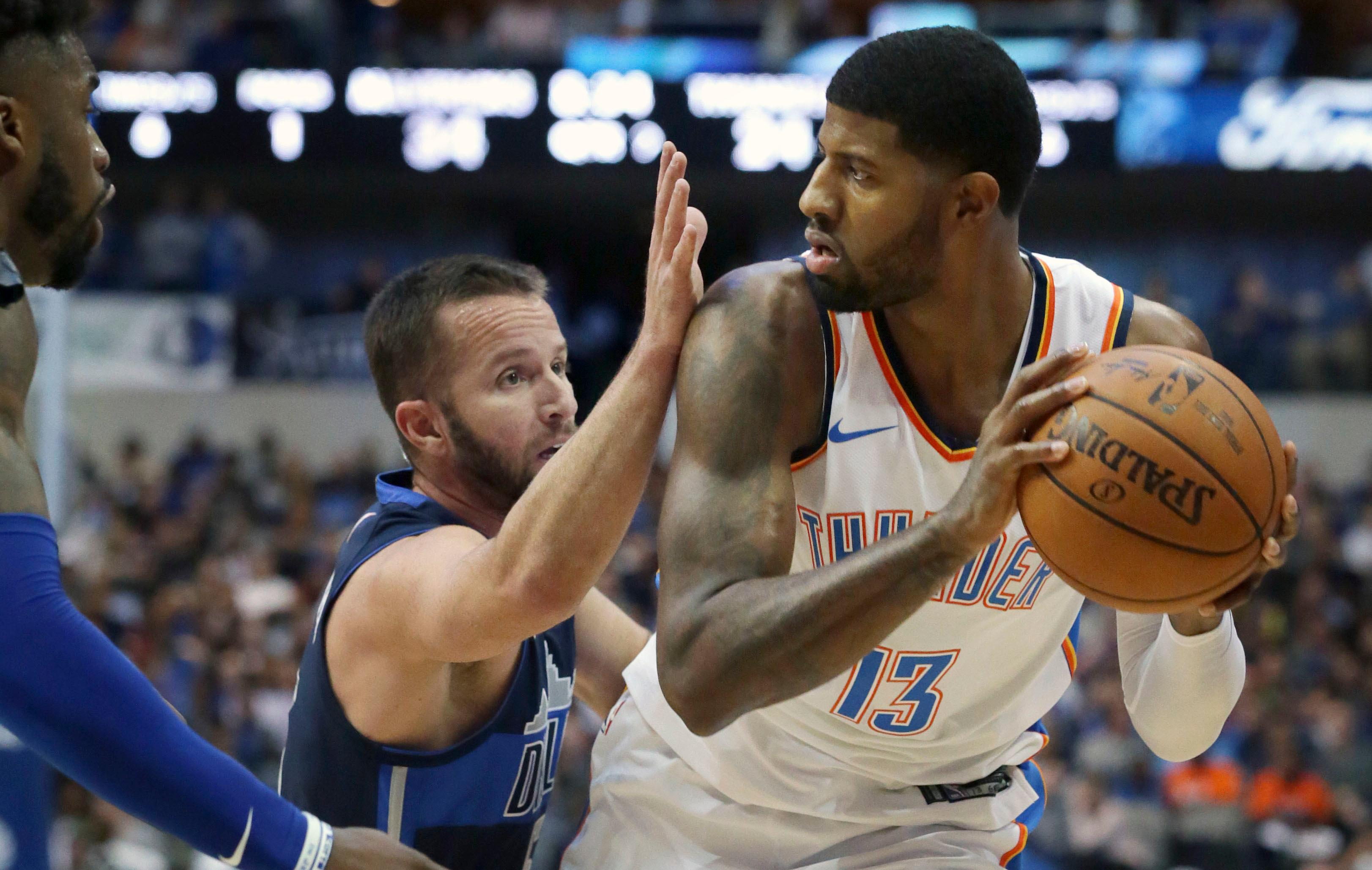 Oklahoma City Thunder forward Paul George (13) looks to pass against Dallas Mavericks defenders J.J. Barea, center, and Wesley Matthews during the first half of an NBA basketball game in Dallas, Saturday, Nov. 25, 2017. (AP Photo/LM Otero)