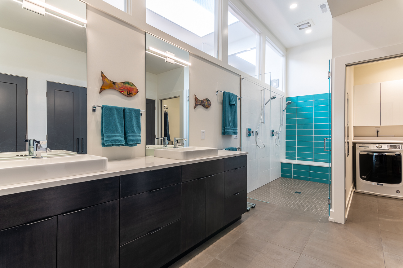 The first-floor bathroom also acts as the master bathroom and laundry room. The bathroom has double vanities and showerheads, and windows at the top of the wall allow the main living area's skylights to redirect natural light into the space. / Image: Phil Armstrong // Published: 10.11.20