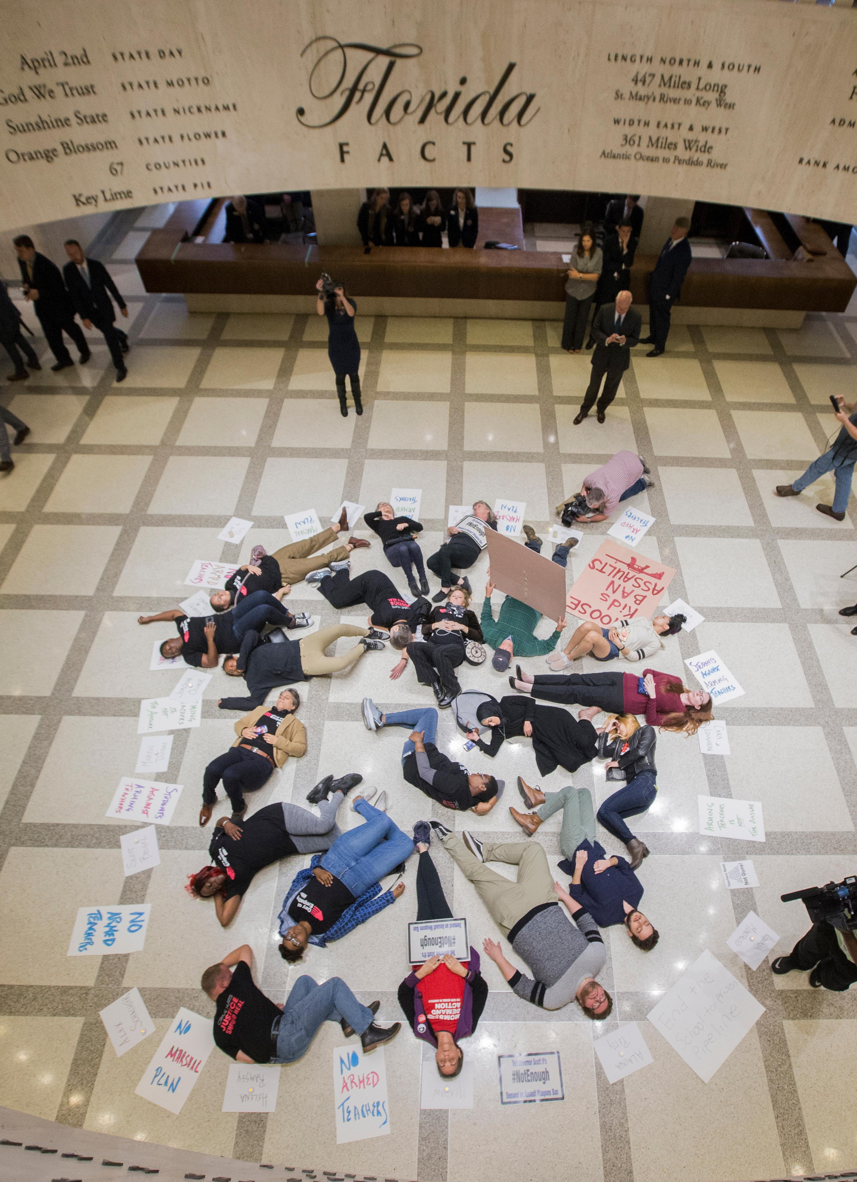 A group of 20 college students and activists stage a die-in on the 4th floor rotunda between the House and Senate chambers while the House takes up the school safety bill at the Florida Capital in Tallahassee, Fla., Tuesday, March 6, 2018. (AP Photo/Mark Wallheiser)