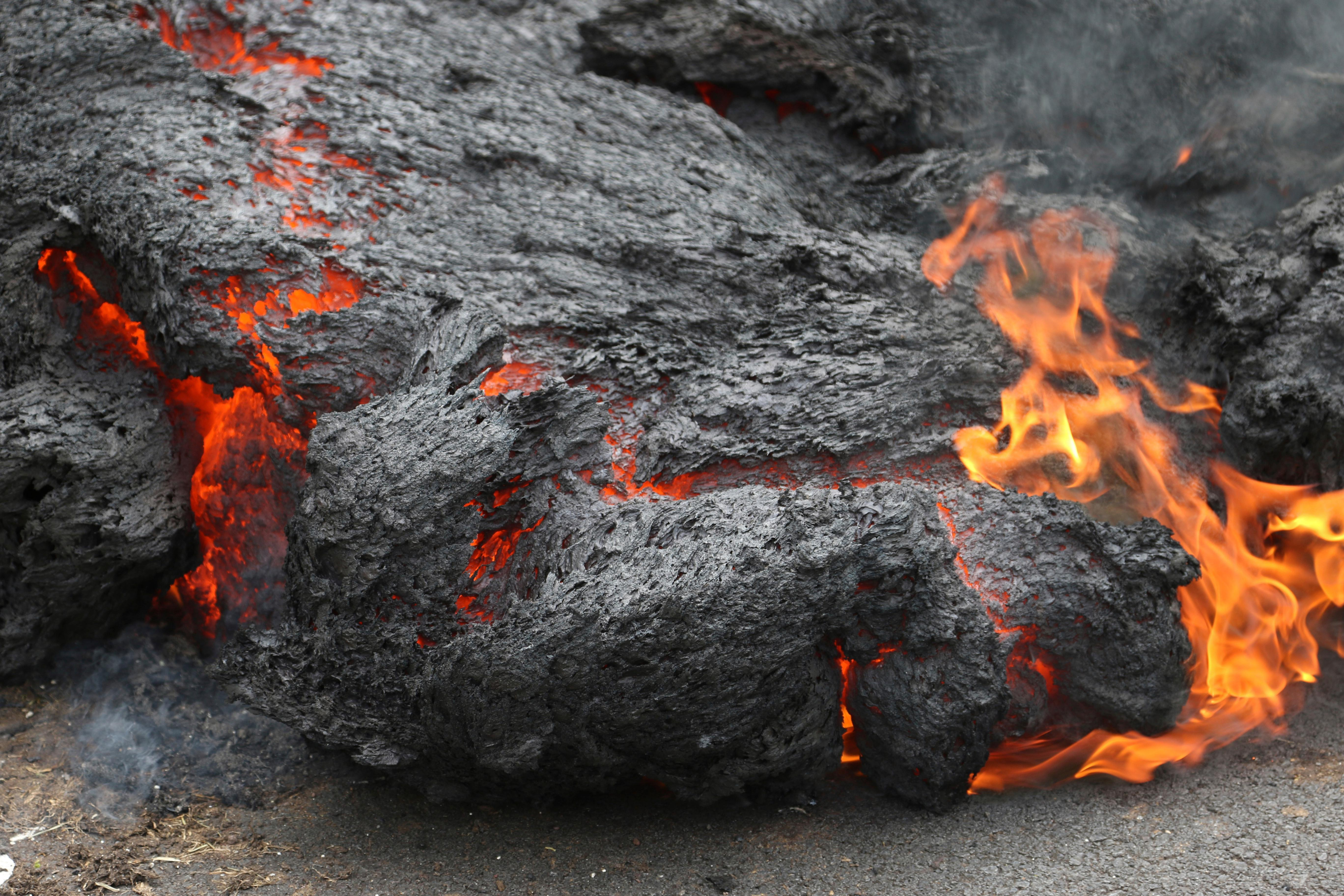File - In this May 5, 2018, file photo, lava burns across a road in the Leilani Estates subdivision near Pahoa, Hawaii. The lava hisses, crackles and pops. It roars like an engine as it sloshes and bubbles. It shoots into the sky, bright orange and full of danger, or oozes along the pavement, a giant bubbling blob of black marshmallow-like fluff, crushing homes and making roads impassable. (AP Photo/Caleb Jones, File)