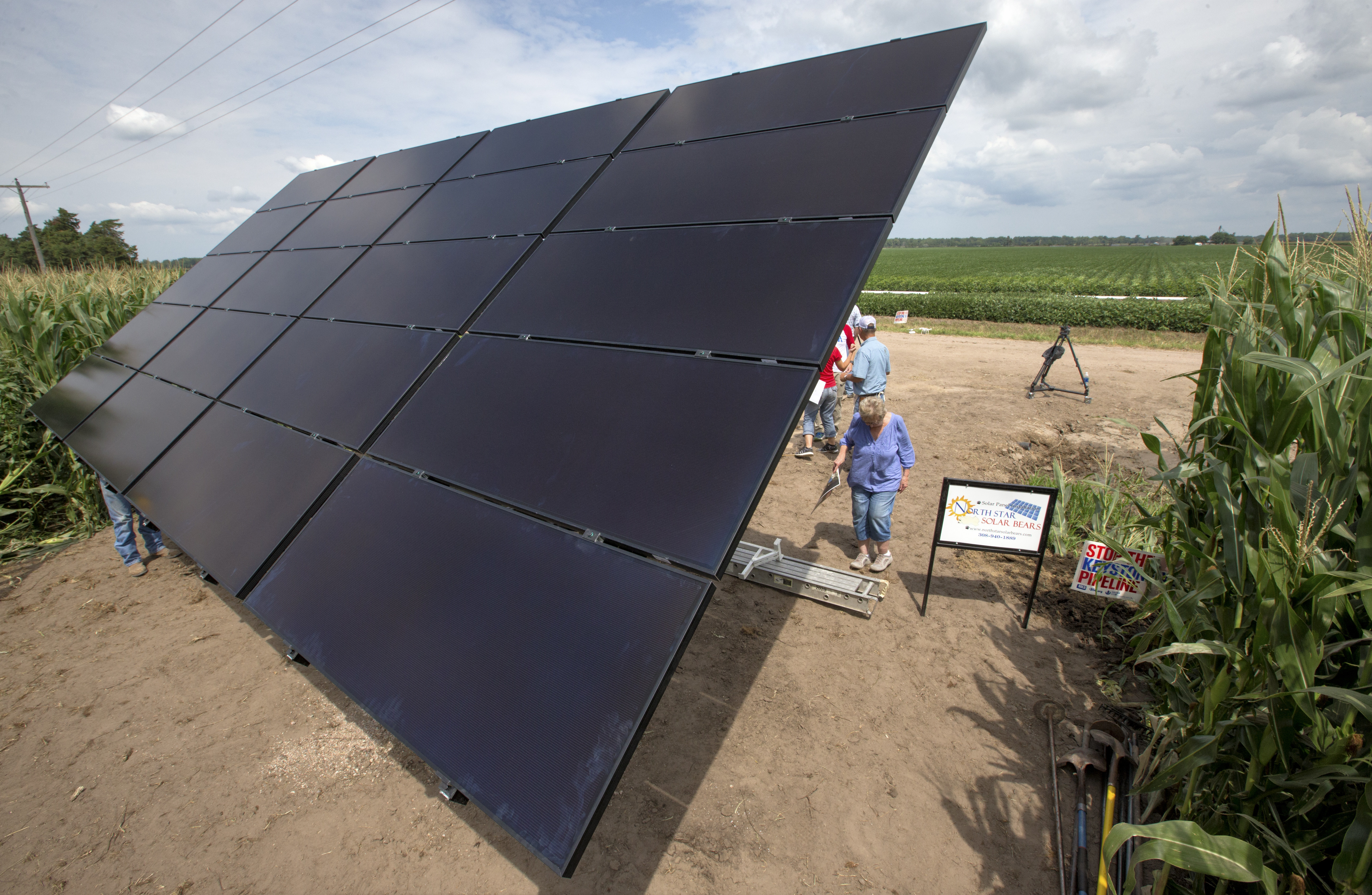 In this July 29, 2017 photo, an array of solar panels is seen on the land of corn farmer Jim Carlson of Silver Creek, Ne., in the proposed path of the Keystone XL pipeline. Despite new uncertainty over whether TransCanada, the builder of the Keystone XL pipeline will continue the project, longtime opponents in Nebraska aren't letting their guard down and neither are law enforcement officials who may have to react to protests if it wins approval. (AP Photo/Nati Harnik)