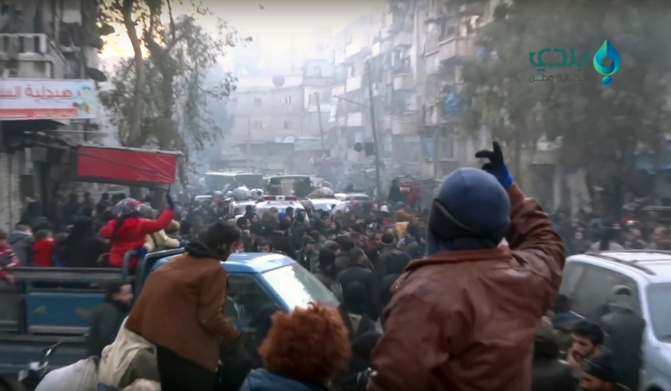 This frame grab from video provided by Baladi News Network, a Syrian opposition media outlet that is consistent with independent AP reporting, shows civilians gathering for evacuation from eastern Aleppo, Syria, Thursday, Dec. 15, 2016. The Russian military said over 1,000 people have been evacuated from Aleppo under a cease-fire deal reached with Syrian rebels. France's ambassador to the United Nations says international observers should monitor the safe evacuation of civilians and fighters from the war-torn Syrian city of Aleppo. (Baladi News Network via AP)